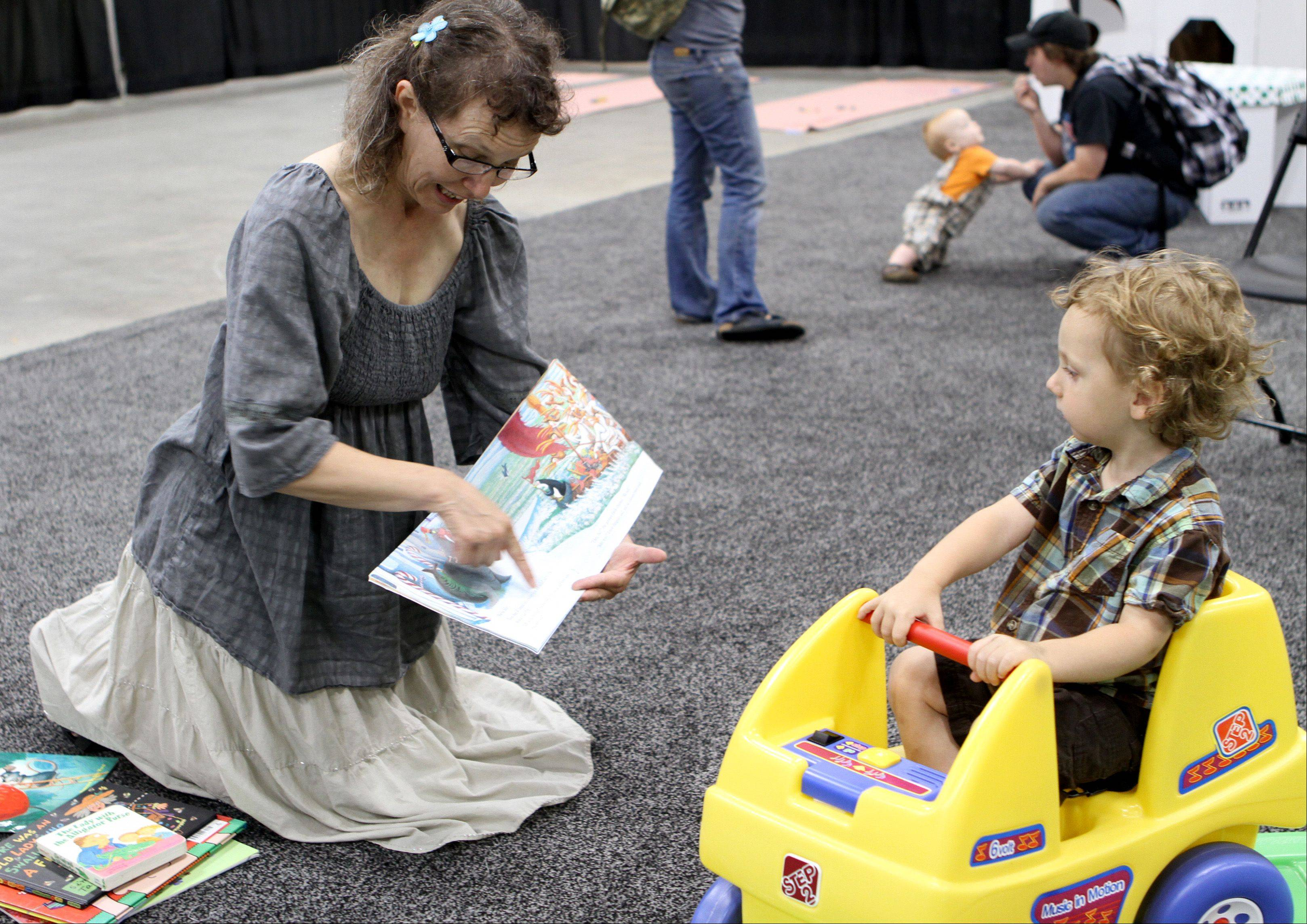 Sharon price of Palatine reads a story to Vincent Polizzi, 2, from West Dundee, during Bebe Paluzza Sunday afternoon at the Schaumburg Convention Center. Vendors showcased products for soon-to-be parents and current parents of babies and toddlers.