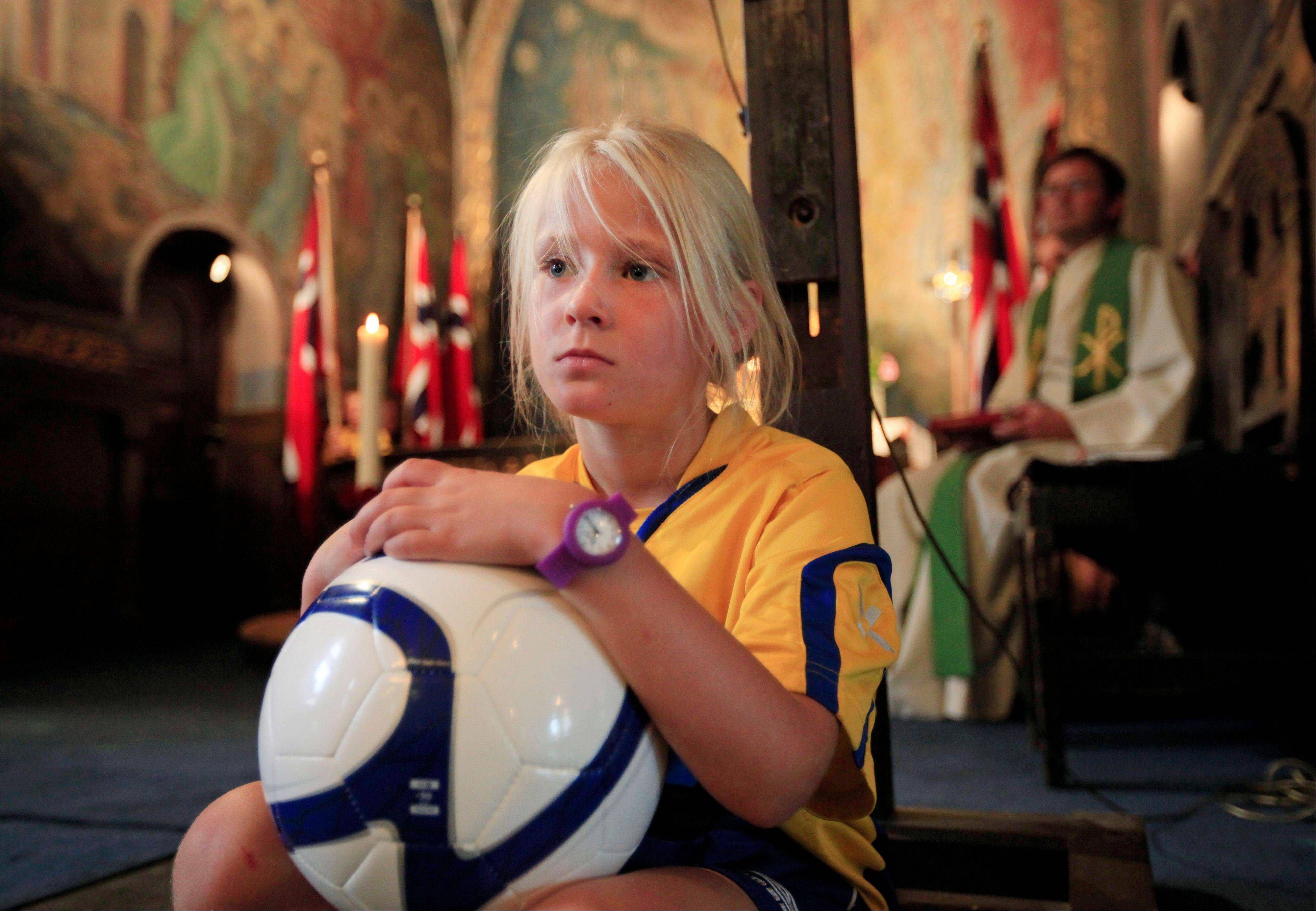 A schoolchild, participating in an international youth soccer tournament, attends a commemoration memorial for the victims of July 22 bomb attack and shooting rampage in Oslo on Sunday.