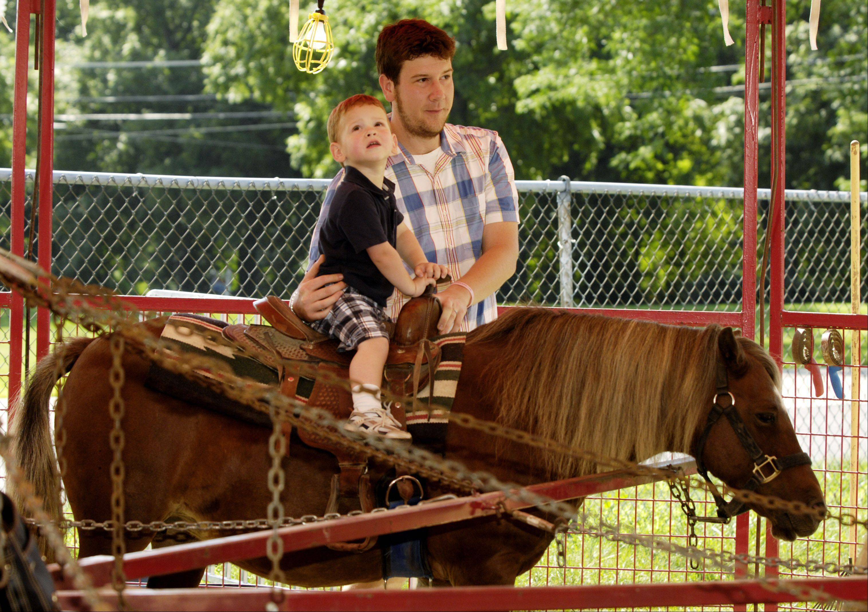 Matt Golas of Naperville takes his 2 1/2 year son Theo for a pony ride.