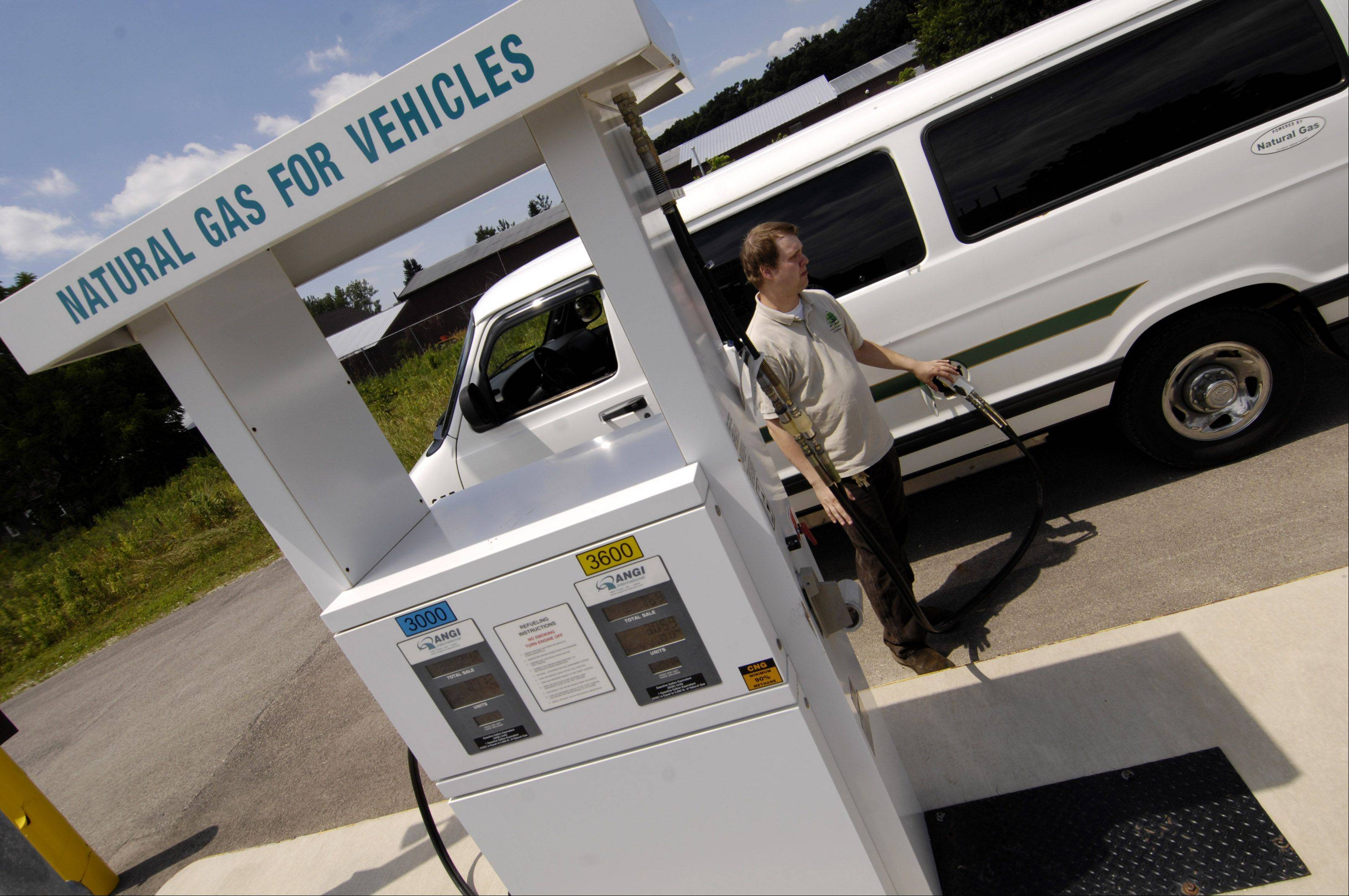 Christopher Lyon, assistant to the manager of fleet services at the Forest Preserve District of DuPage County, fuels a van with compressed natural gas at the Blackwell Forest Preserve fueling station.