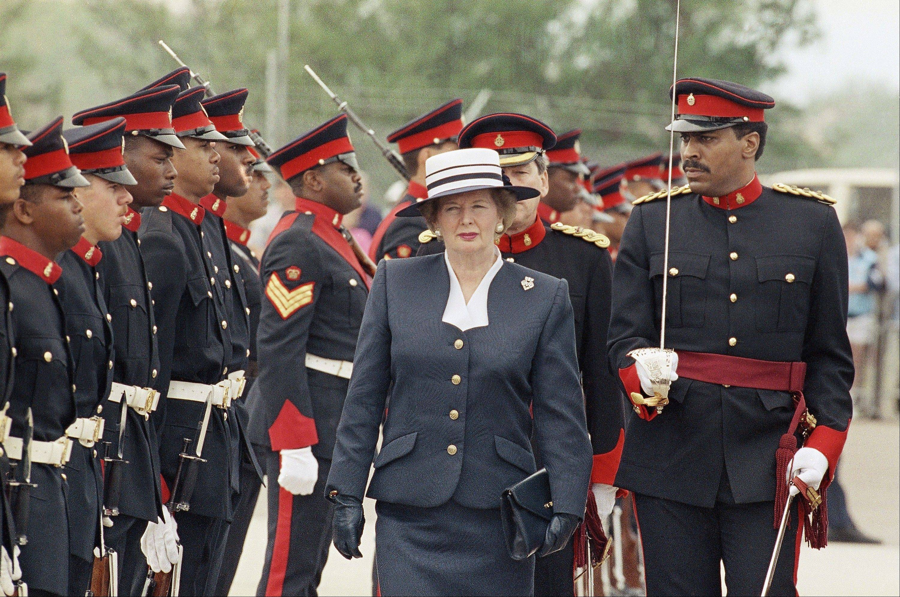 Margaret Thatcher, then British prime minister, reviews the troops at the Bermuda airport in Hamilton after a flight from London. Bermuda is one of 16 territories listed by the U.N. as awaiting decolonization.