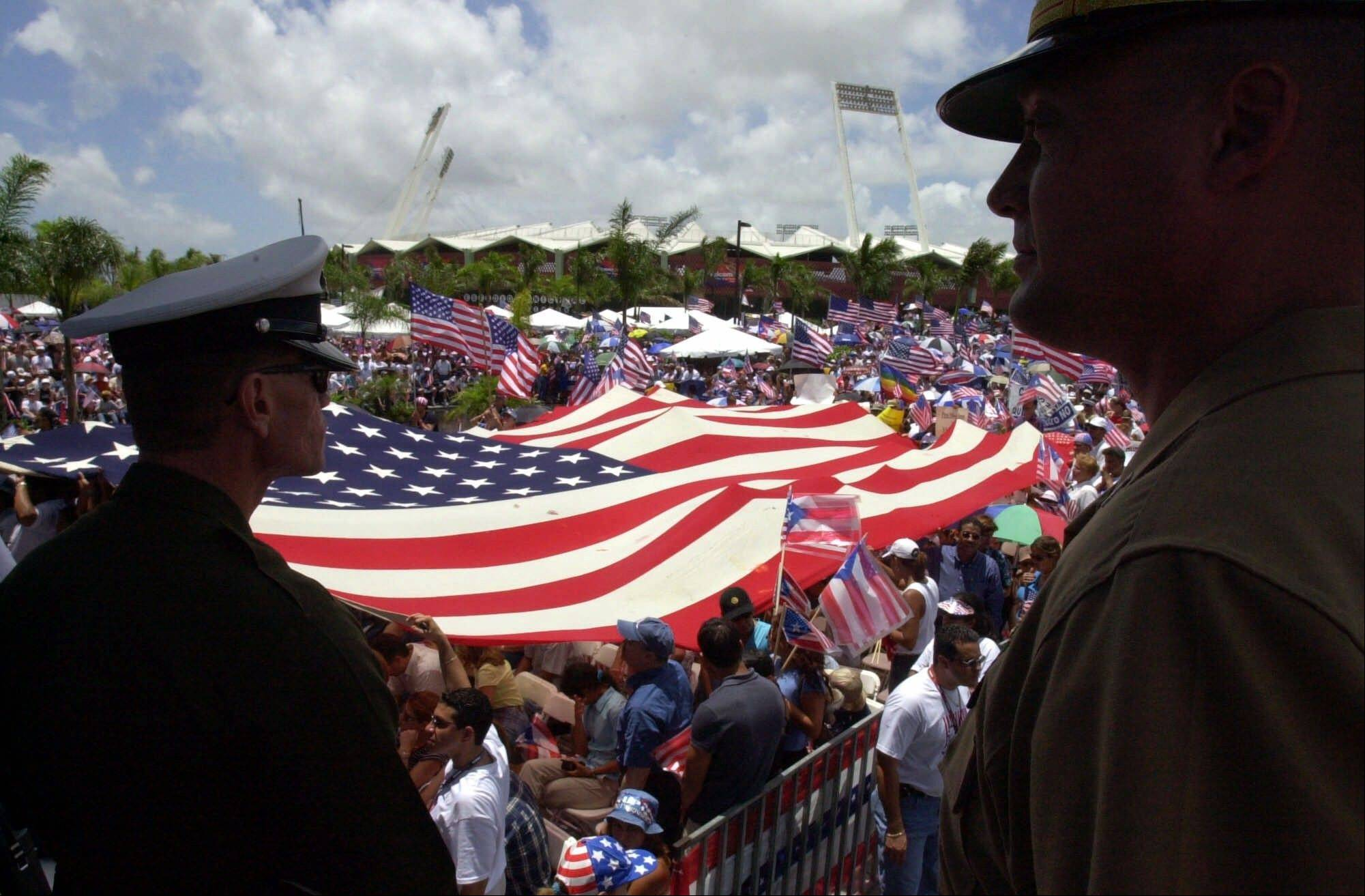 Marine Capt. Scott Madziarczyk of Chicago, right, looks over a crowd of Puerto Ricans celebrating the United States of America's Independence Day in San Juan. Although Puerto Rico was removed from the list of territories kept by the U.N. Special Committee on Decolonization when it became a U.S. commonwealth in 1953, the committee annually adopts a Cuban motion calling for Puerto Rico's self-determination.