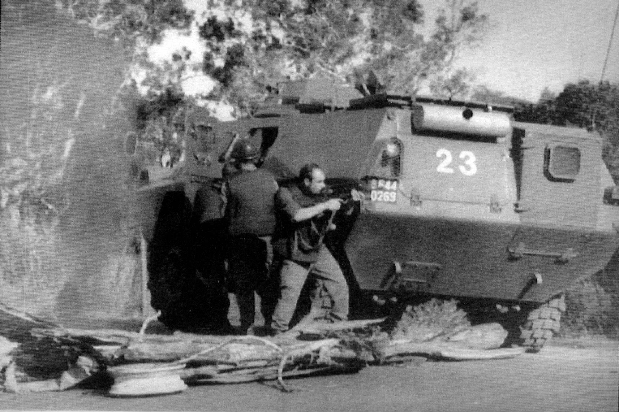 A gendarme aims his weapon as an armored vehicle destroys a barricade erected by independence fighters near Saint-Louis, on the French Pacific island of New Caledonia. Seven policemen were injured in clashes as New Caledonians voted in France's presidential election. Islanders are expected to vote on independence in a referendum in 2014.
