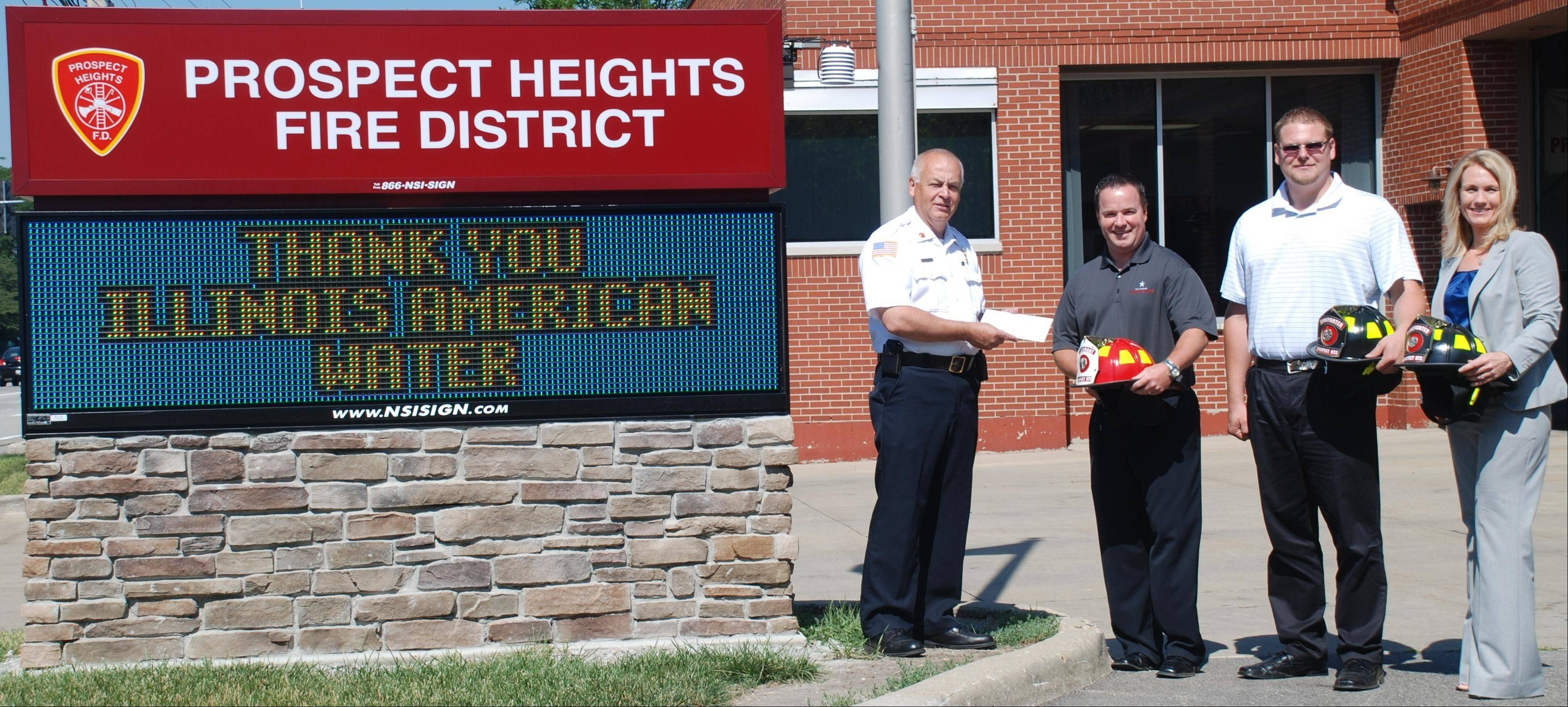 Fire Chief Donald Gould, Michael Smyth, Timothy Morris and Susan Gram from Illinois American Water, who presented a grant check for $1,500 to the Prospect Heights Fire Protection District for the purchase of new fire helmets.