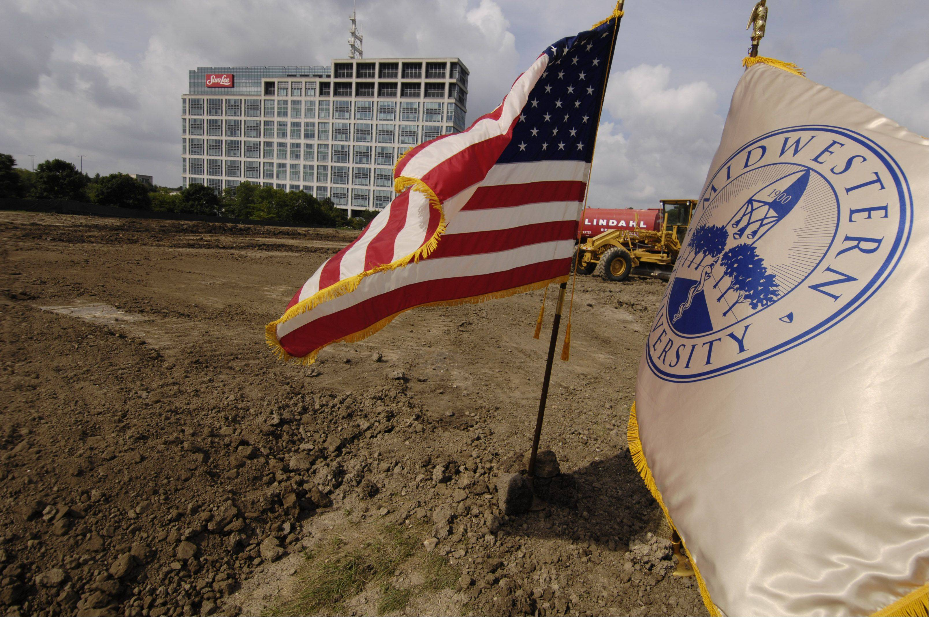 The American and Midwestern University flags fly during the ground breaking ceremony for the new Midwestern University clinic in Downers Grove.