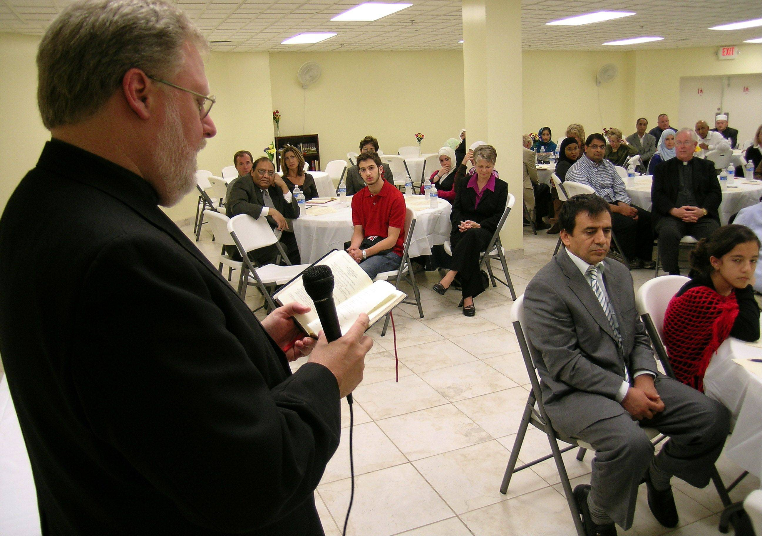 "The Rev. Thomas A. Baima, provost at the University of Saint Mary of the Lake Mundelein Seminary, reads a Bible verse during an interfaith ""iftar,"" or the Muslim fast-breaking meal, at Islamic Foundation North's mosque in Libertyville."