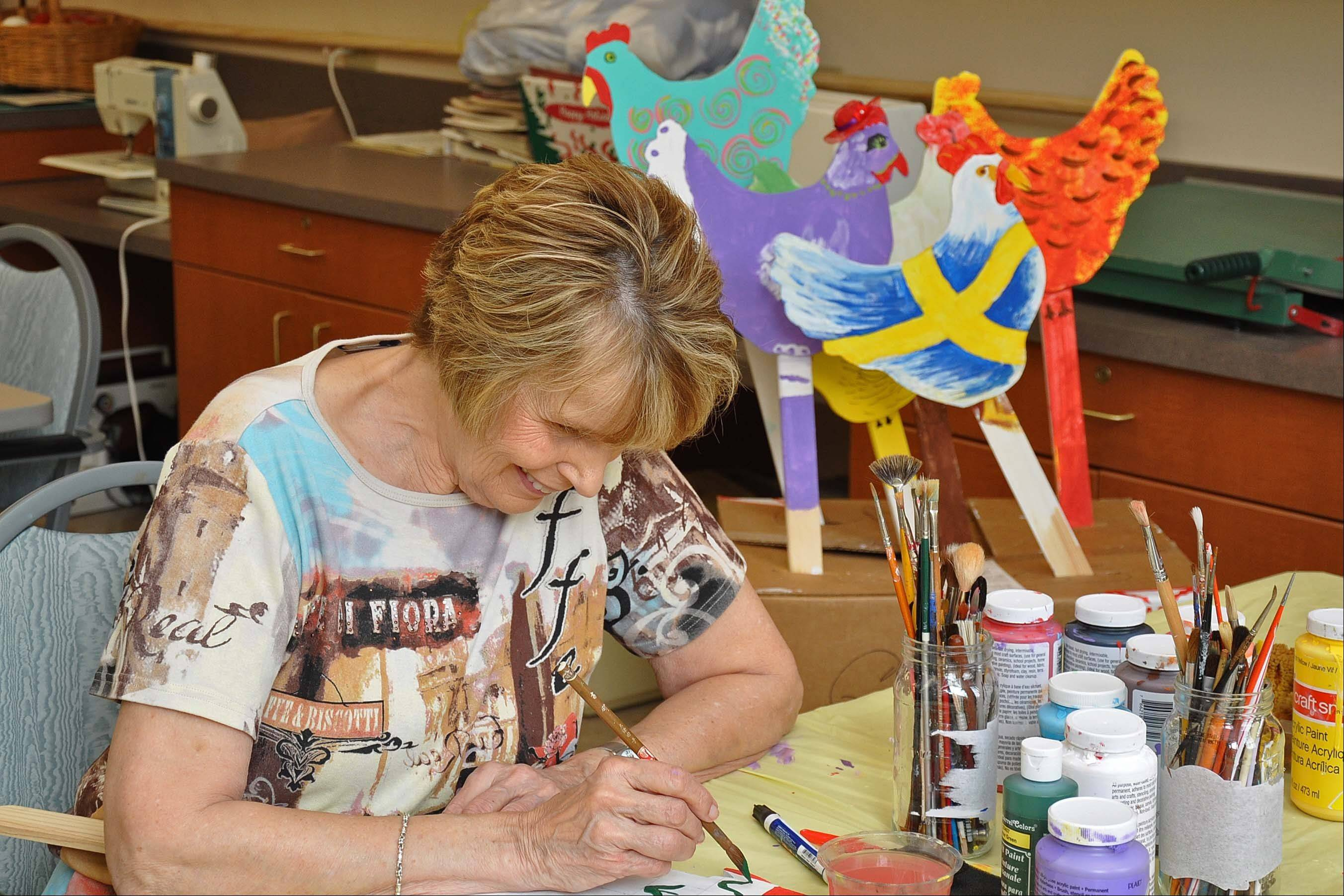 Phyllis Howat paints a chicken for display at the Holmstad, a retirement community in Batavia.