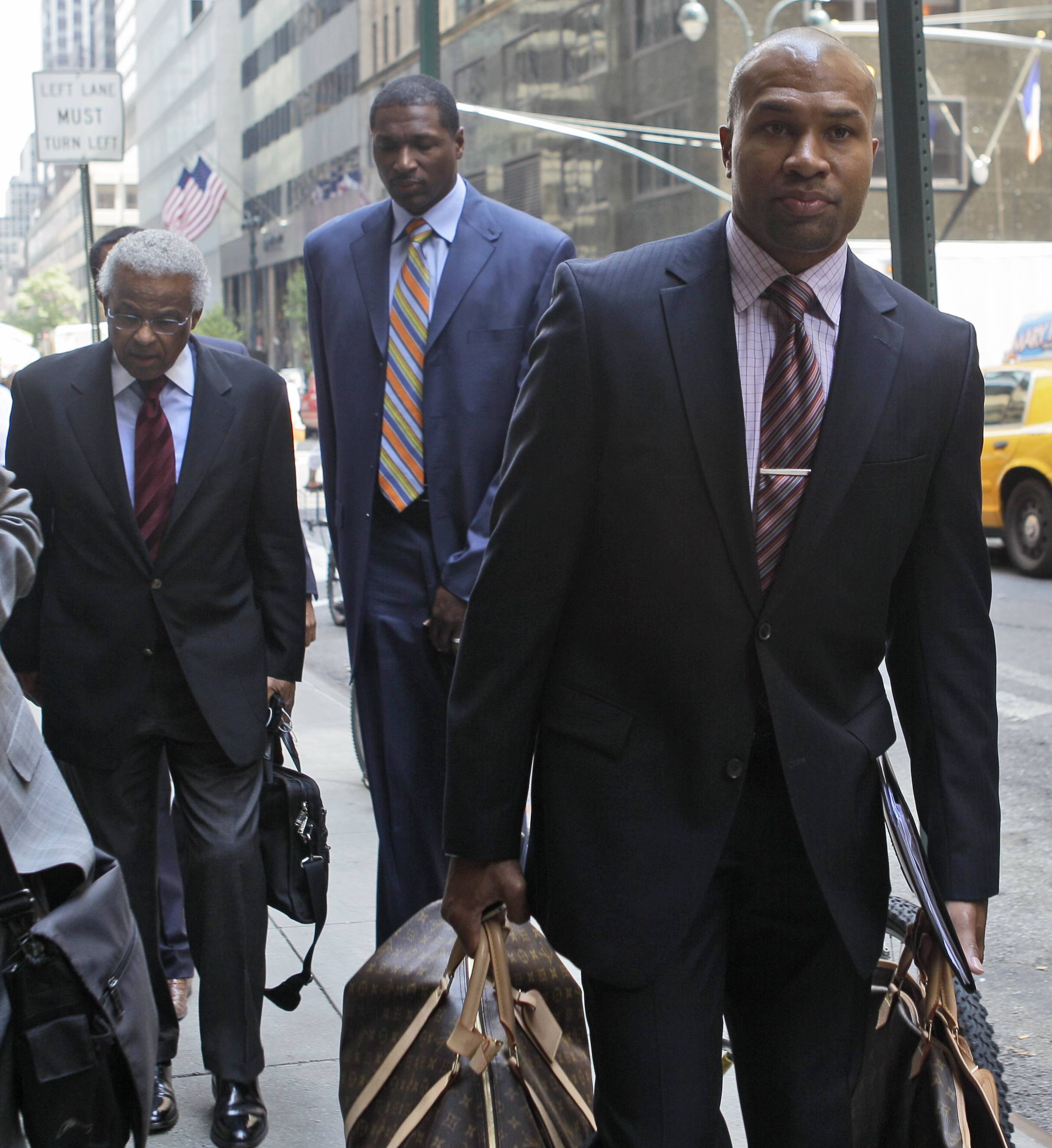 NBA Players Association president Derek Fisher, right, NBA union chief Billy Hunter, left, and LA Lakers' Theo Ratliff arrive at a midtown hotel for a meeting with the NBA Monday. One month after the lockout began, and three months before the season is scheduled to start, representatives for the NBA owners and locked-out players return to the bargaining table.