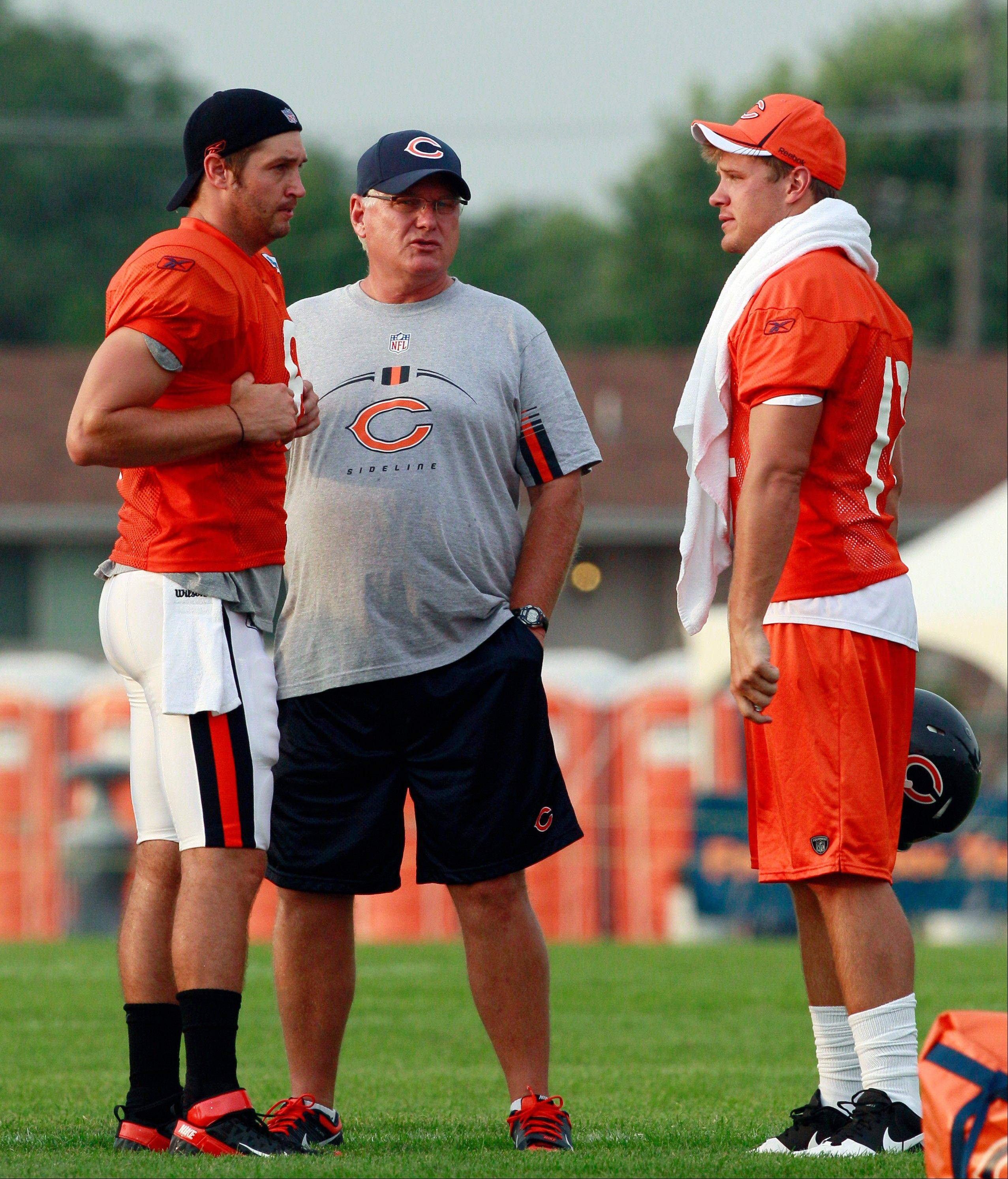 Bears offensive coordinator Mike Martz, center, talks with quarterbacks Jay Cutler, left, and Caleb Hanie during camp Monday. On Tuesday, Martz told reporters he was �giddy� watching Cutler�s improved dropbacks and footwork.