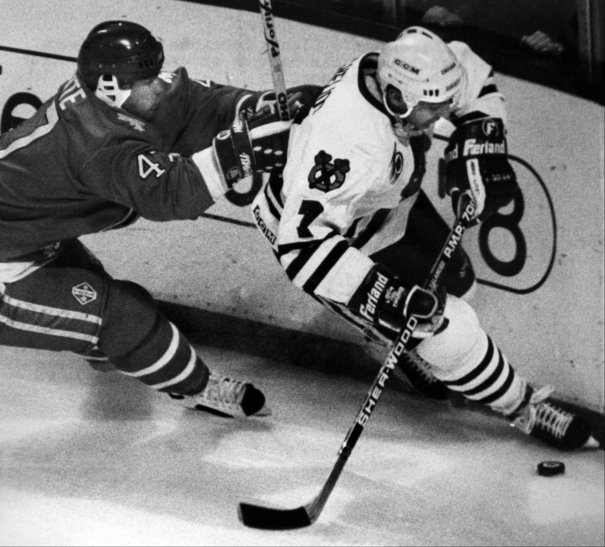 Chris Chelios of the Blackhawks, right, moves the puck as he tries to avoid a push by Claude LaPointe of the Quebec Nordiques on Nov. 8, 1991. Chelios, who became the second-oldest player on the ice in an NHL game on Jan. 8, 2008, was named to the Hall of Fame Monday.