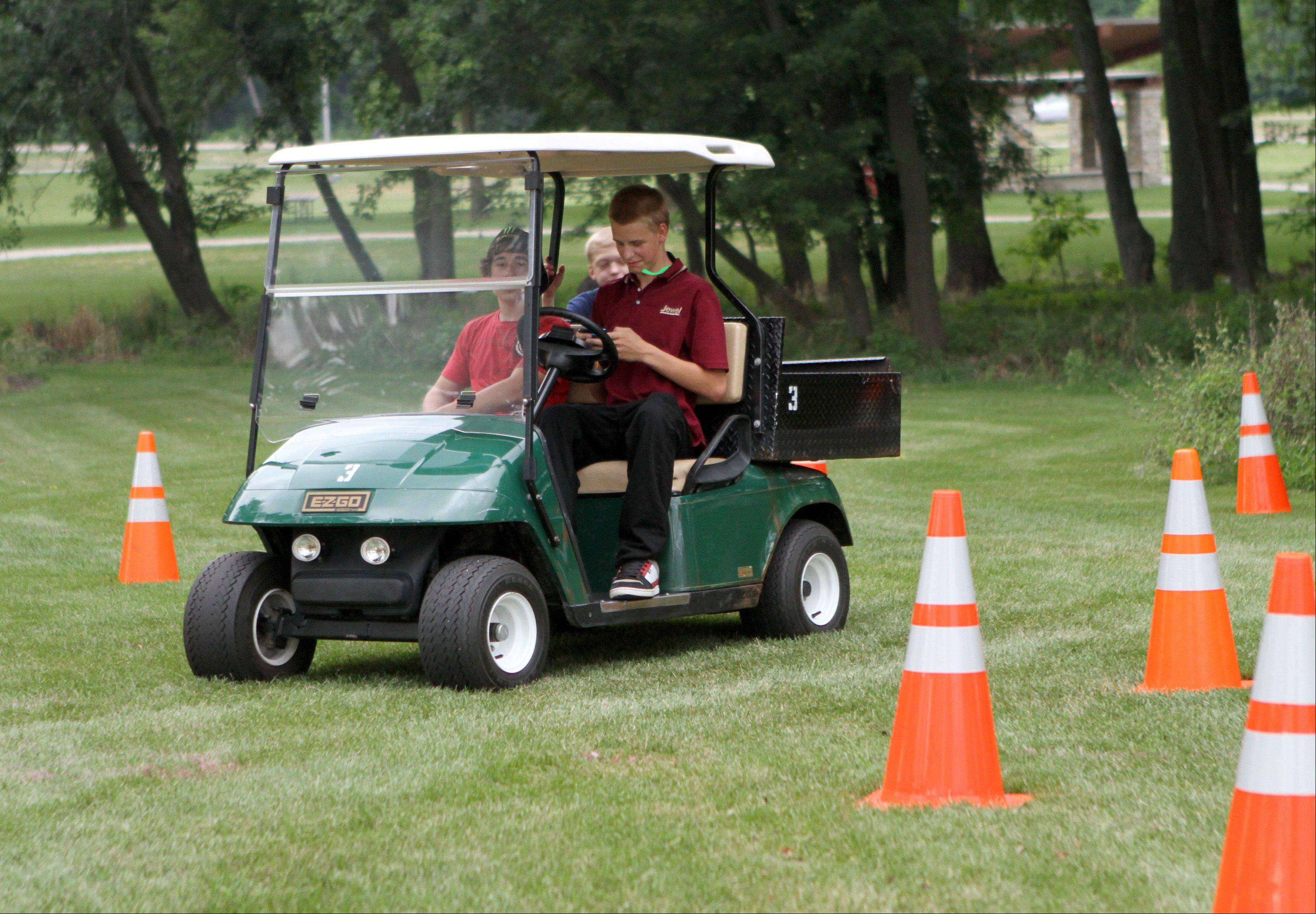 Chase Arbuthnot, 16, right, from Barrington tries to text while driving a golf cart on a setup course at the National Night Out at Citizens Park in Barrington. Dominic Calabres, 15, left, from Barrington also tried the course.