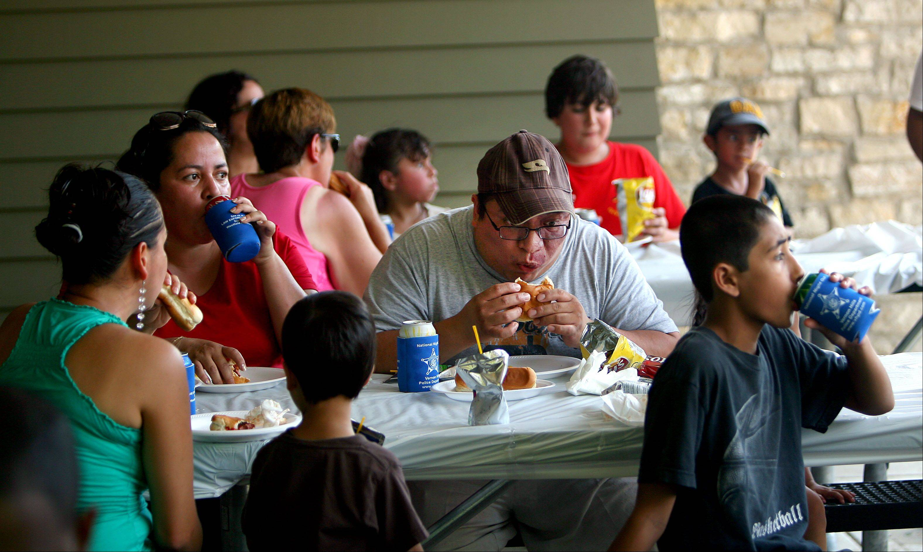 People enjoy some food courtesy of the Vernon Hills police department during it's National Night Out event at Century Park North in Vernon Hills.