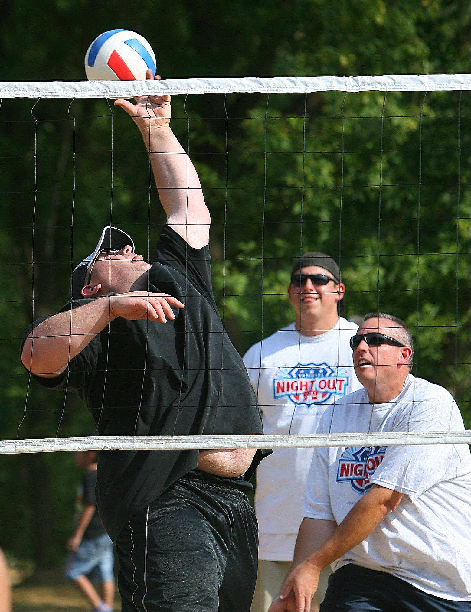 Vernon Hills police officers, from left, Andy Rheintgen, Dan Mead and Todd Williams lay volleyball against local teachers as the department held it's National Night Out event at Century Park North in Vernon Hills.