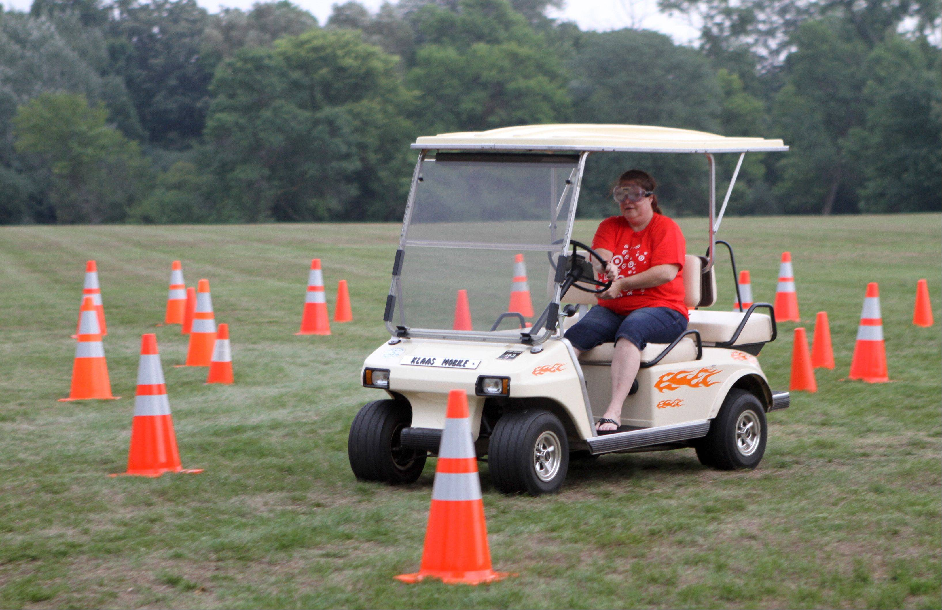 Stephanie Kronberger, from Barrington, wears goggles that simulate drunken driving and drives through a course marked with cones during Barrington's National Night Out at Citizen Park.
