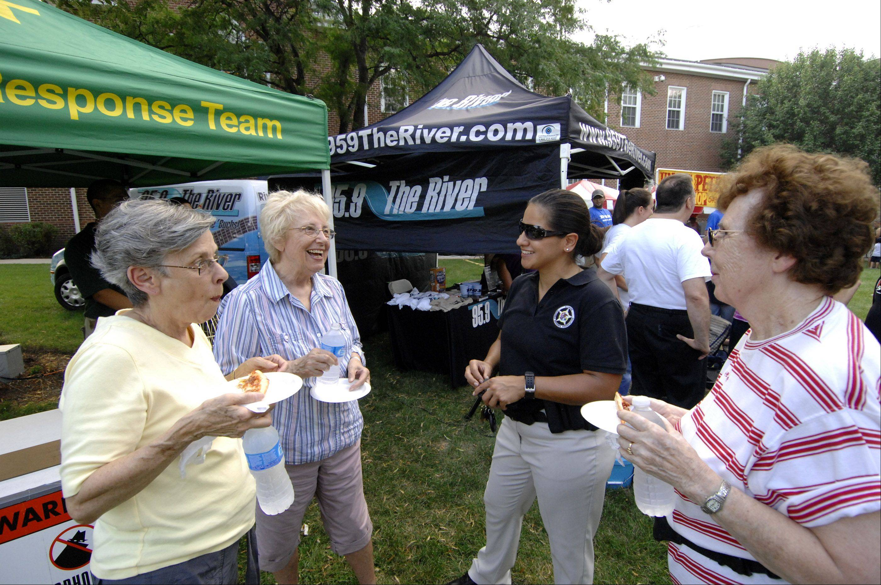 Addison residents turned out in force to chow down on pizza at $1.00 per slice, and participate in National Night Out. The festivities featured local pizza vendors, the police and fire departments and a band on the village hall lawn. Enjoying the pizza and chatting are l-r: Virginia Hardenbrook, Lee Maras, Addison police officer Marie Hernandez, and Rita Seeling.