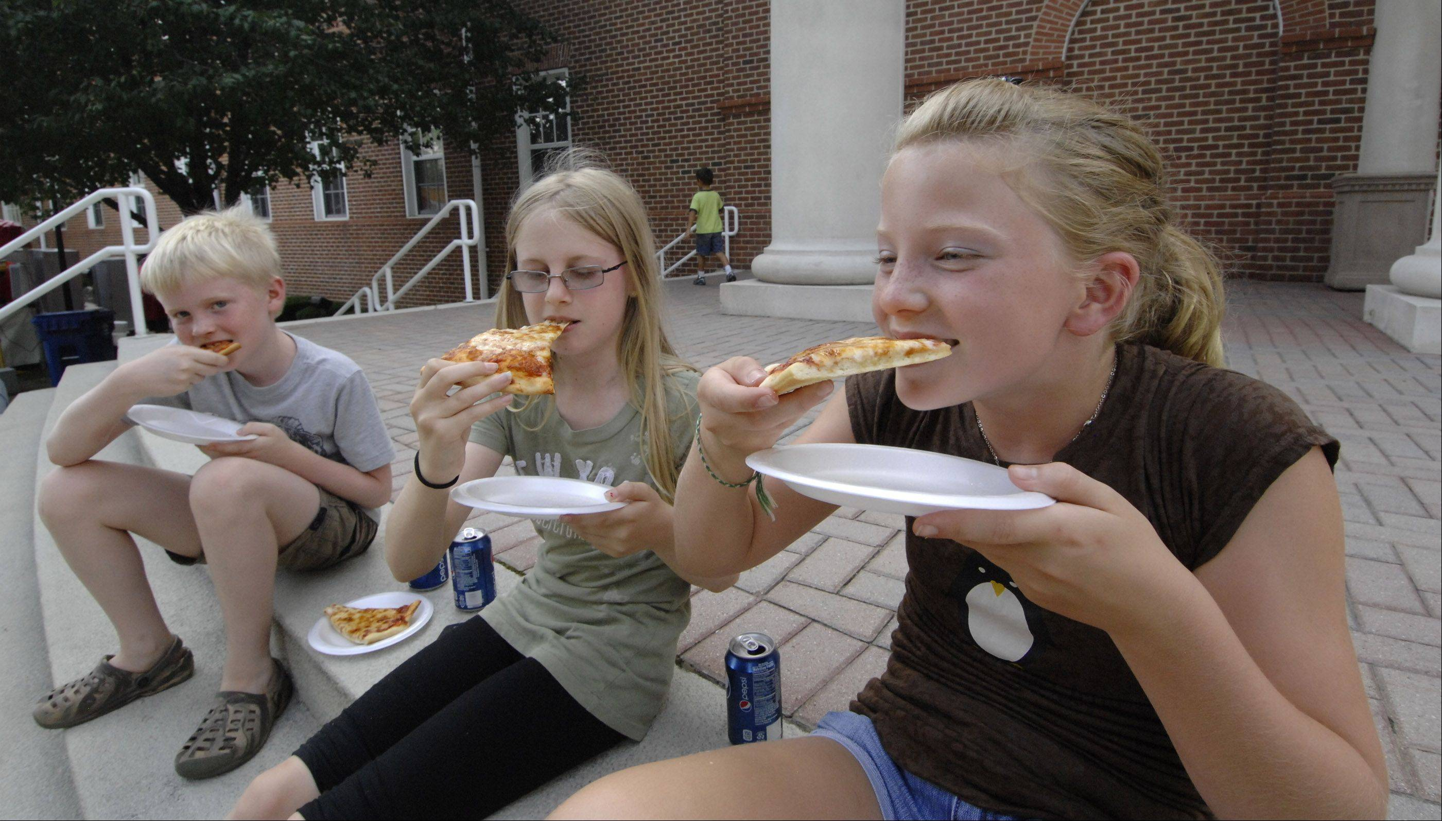 Addison residents l-r, Alex Eddy, Marie Eddy, and Melissa Krefft chow down on pizza at $1.00 per slice, on the village hall steps.