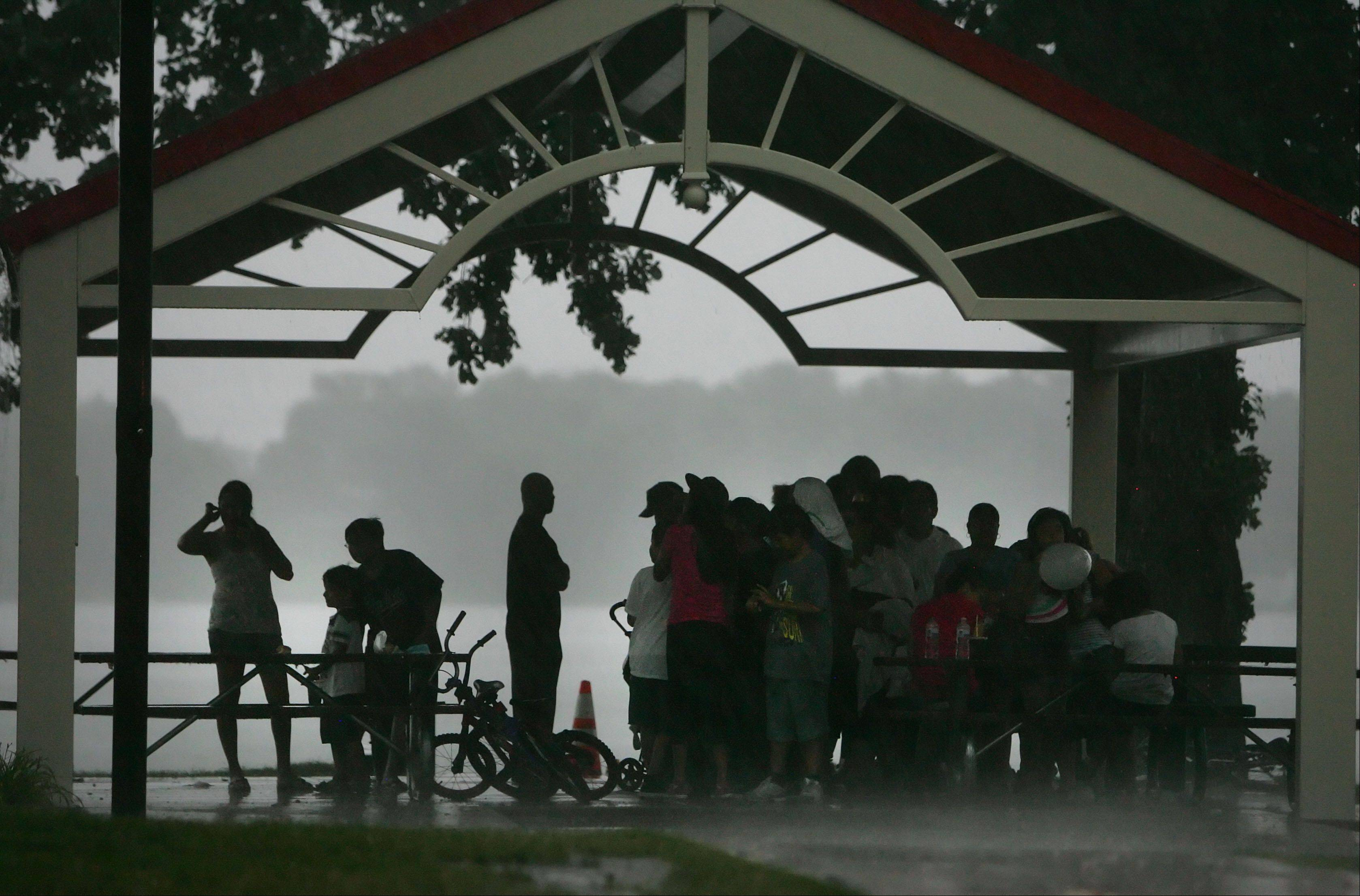 People take cover as a strong thunderstorm moved through the area putting a damper on the National Night Out celebration at Lakefront Park in Round Lake Beach.