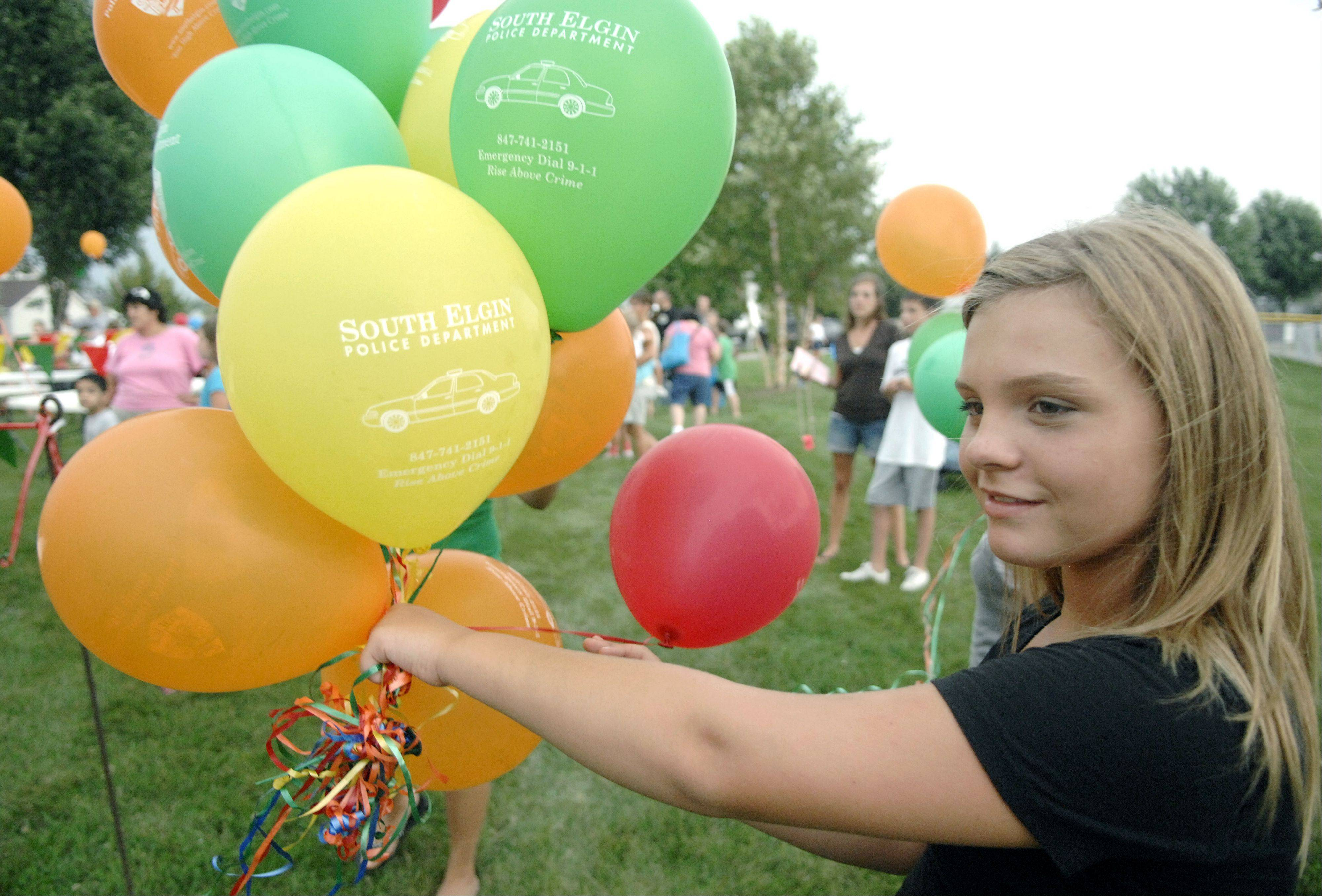 Alyssa Riske, 11, of South Elgin helps pass out balloons for the South Elgin Police Department during National Night Out in Concord Park, Kids were also treated to games, face painting and more.