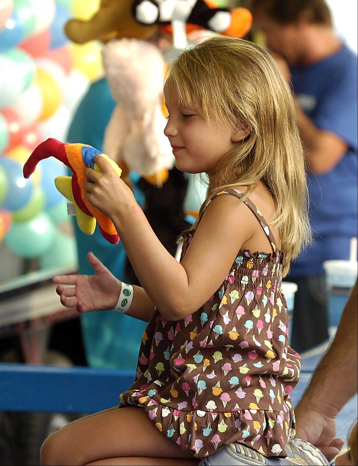Abby Gricius, 5, of Park Ridge selects a toy after she successfully hit a balloon with a dart at the 2010 festival.
