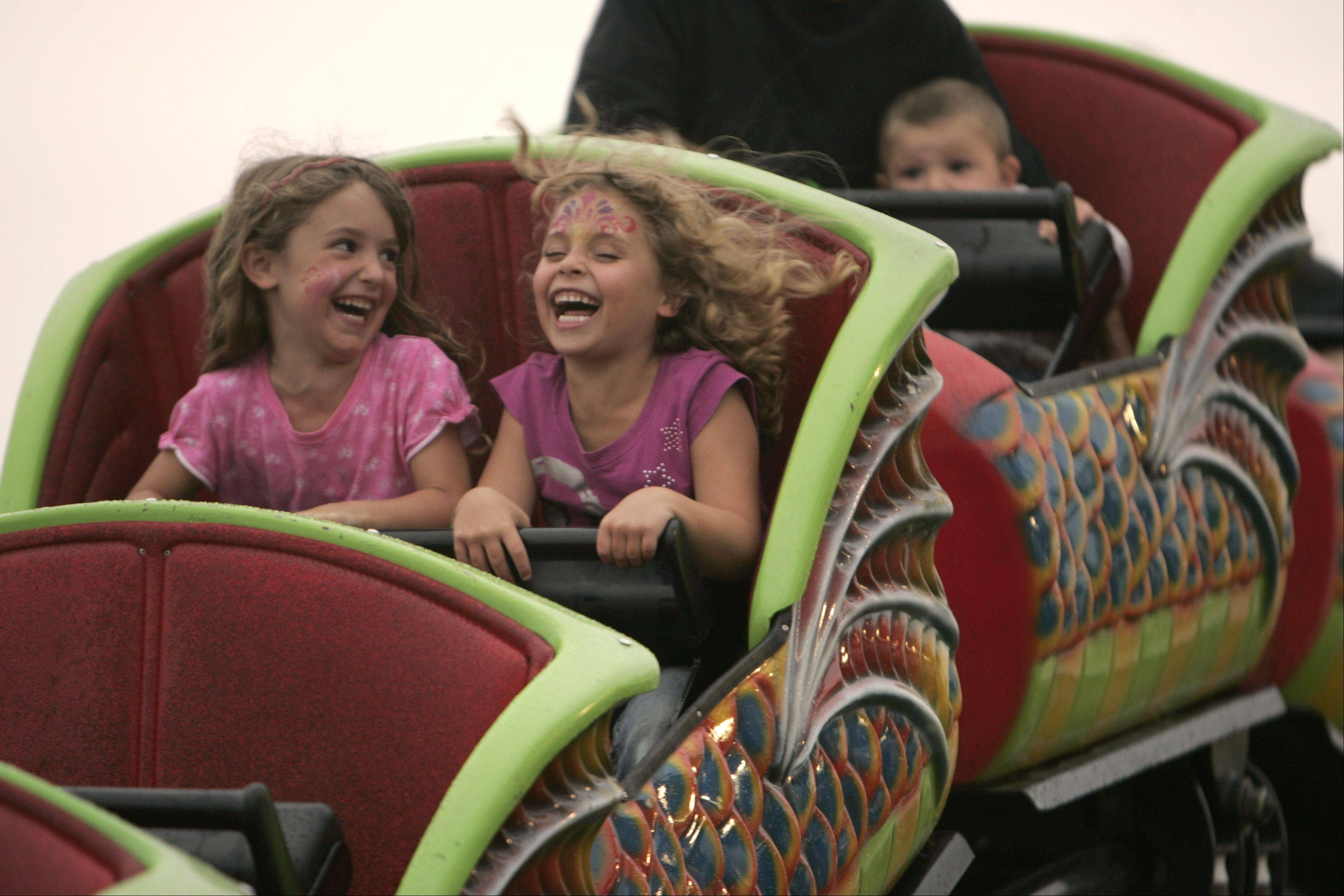 Keira Holtzee, 4, from Woodstock and Kiya Mindard, 5, from Poplar Grove enjoy a carnival ride during the McHenry County Fair in Woodstock.