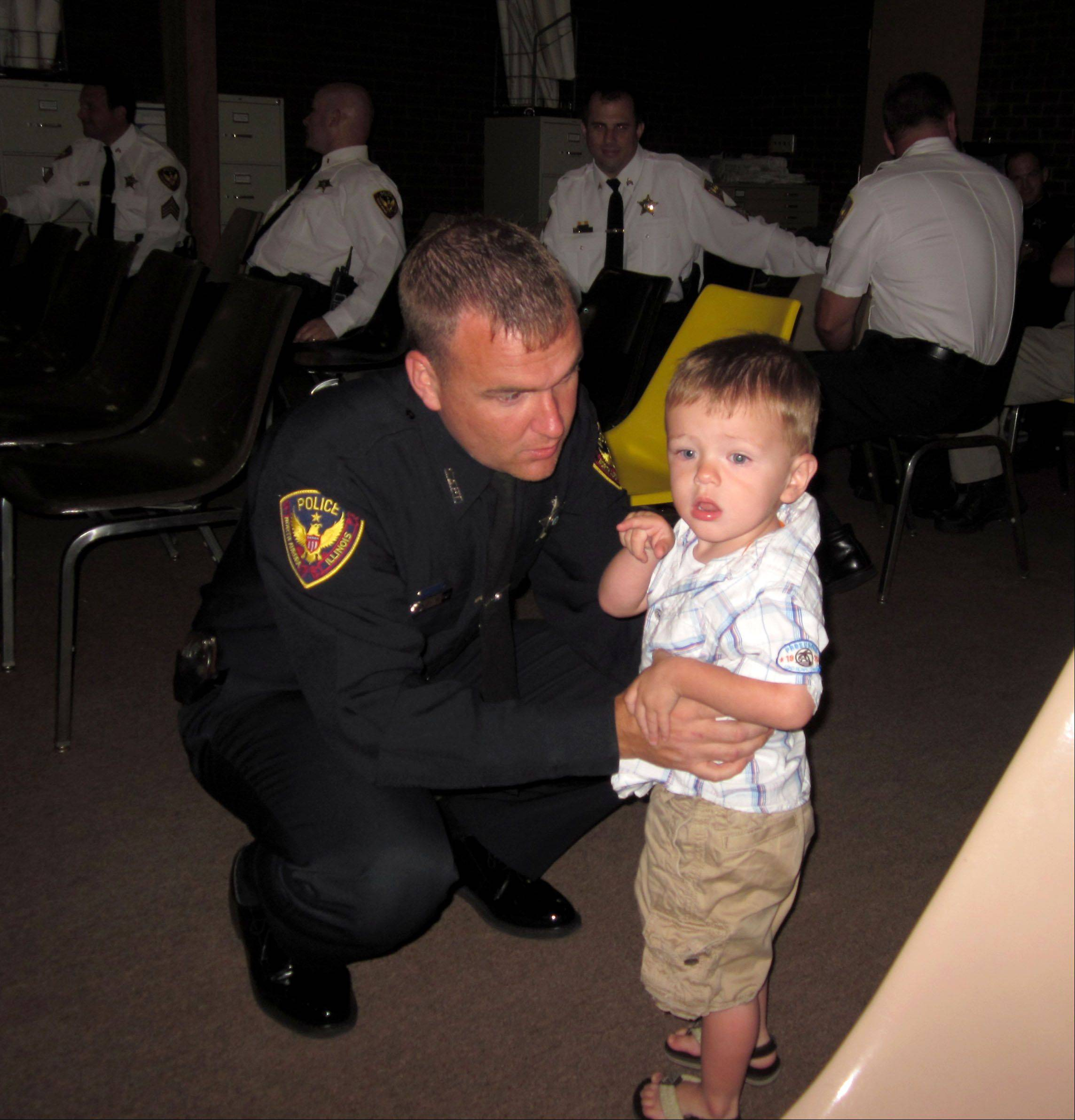 North Aurora Police Officer Michael Quinn, left, speaks to his son, Aidan, before receiving a Medal of Distinguished Service at the North Aurora village board meeting Monday evening. Quinn pulled a man out of a burning car after a three-vehicle crash at Randall and Orchard roads in May.