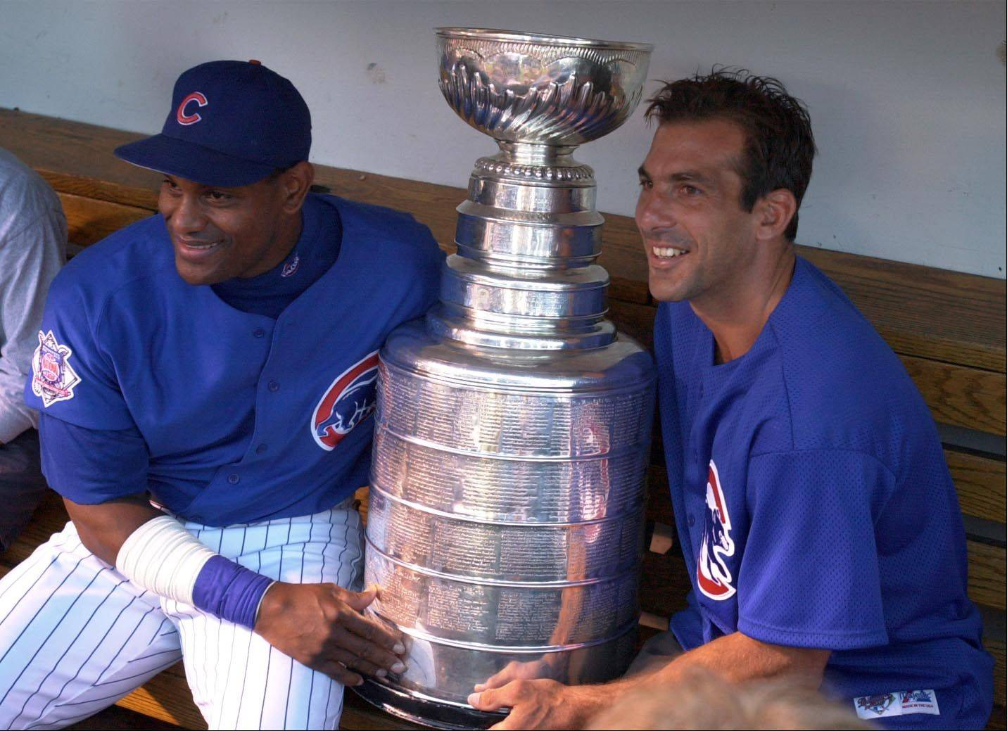 Chris Chelios poses with Sammy Sosa and the Stanley Cup during a Cubs game against Milwaukee.