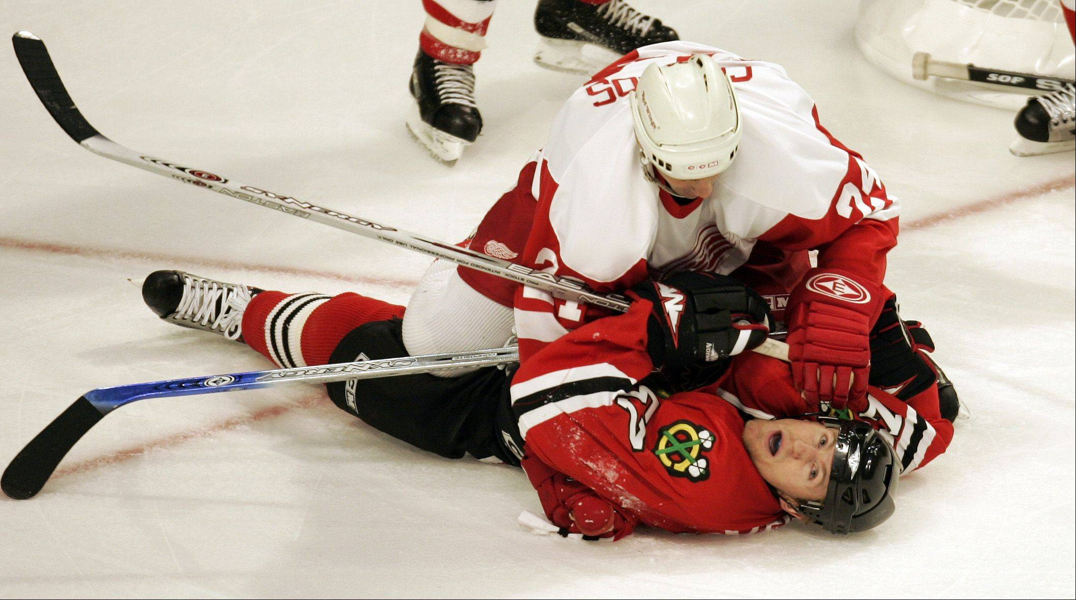 Redwings Chris Chelios pins Hawks Karl Stewart to the ice as he gets checked near the goal in 3rd period in a game against the Chicago Blackhawks at the United Center.