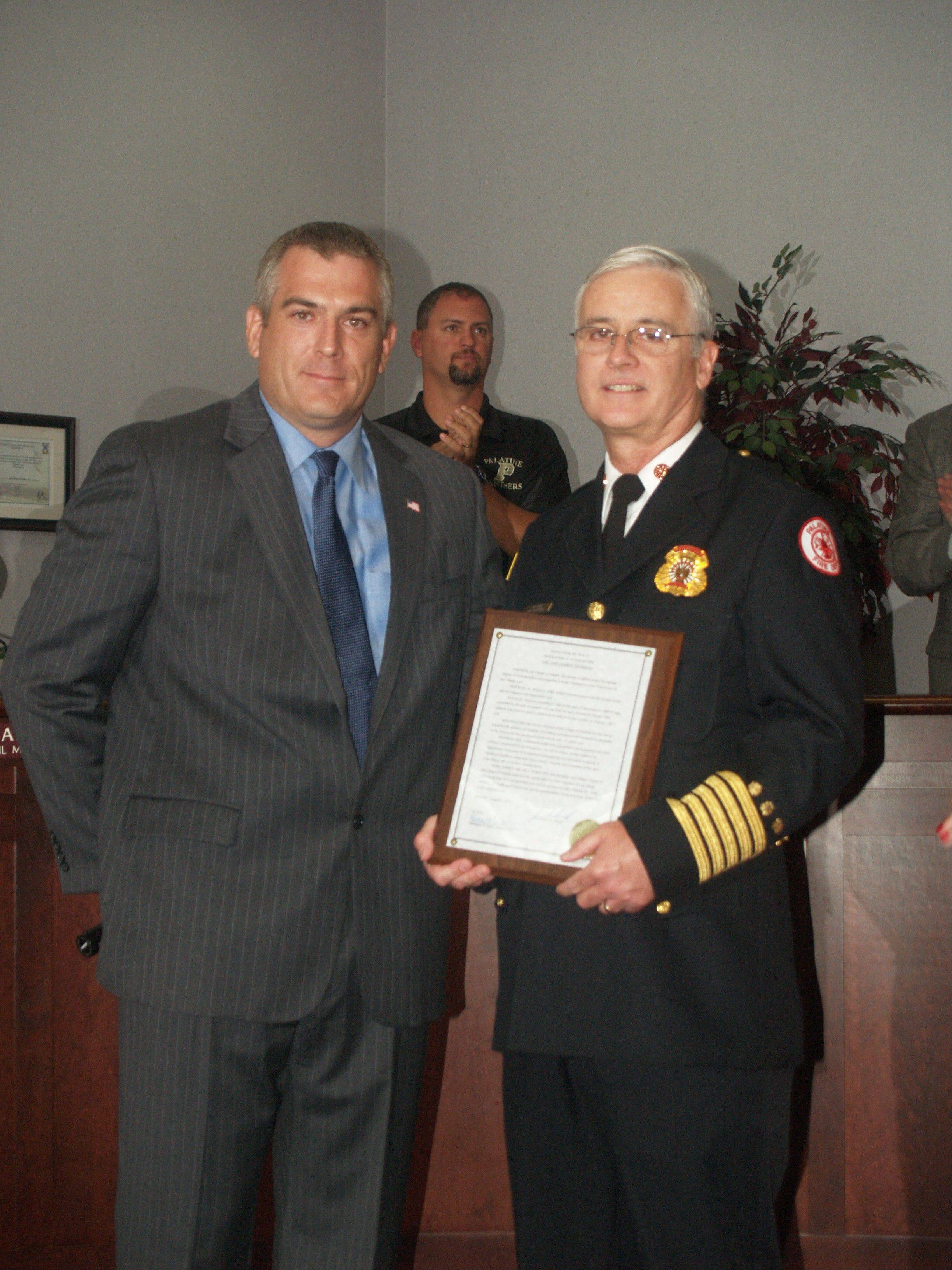 Palatine village President Jim Schwantz presents a plaque to retiring Fire Chief Robert Falardeau at this week's village council meeting.