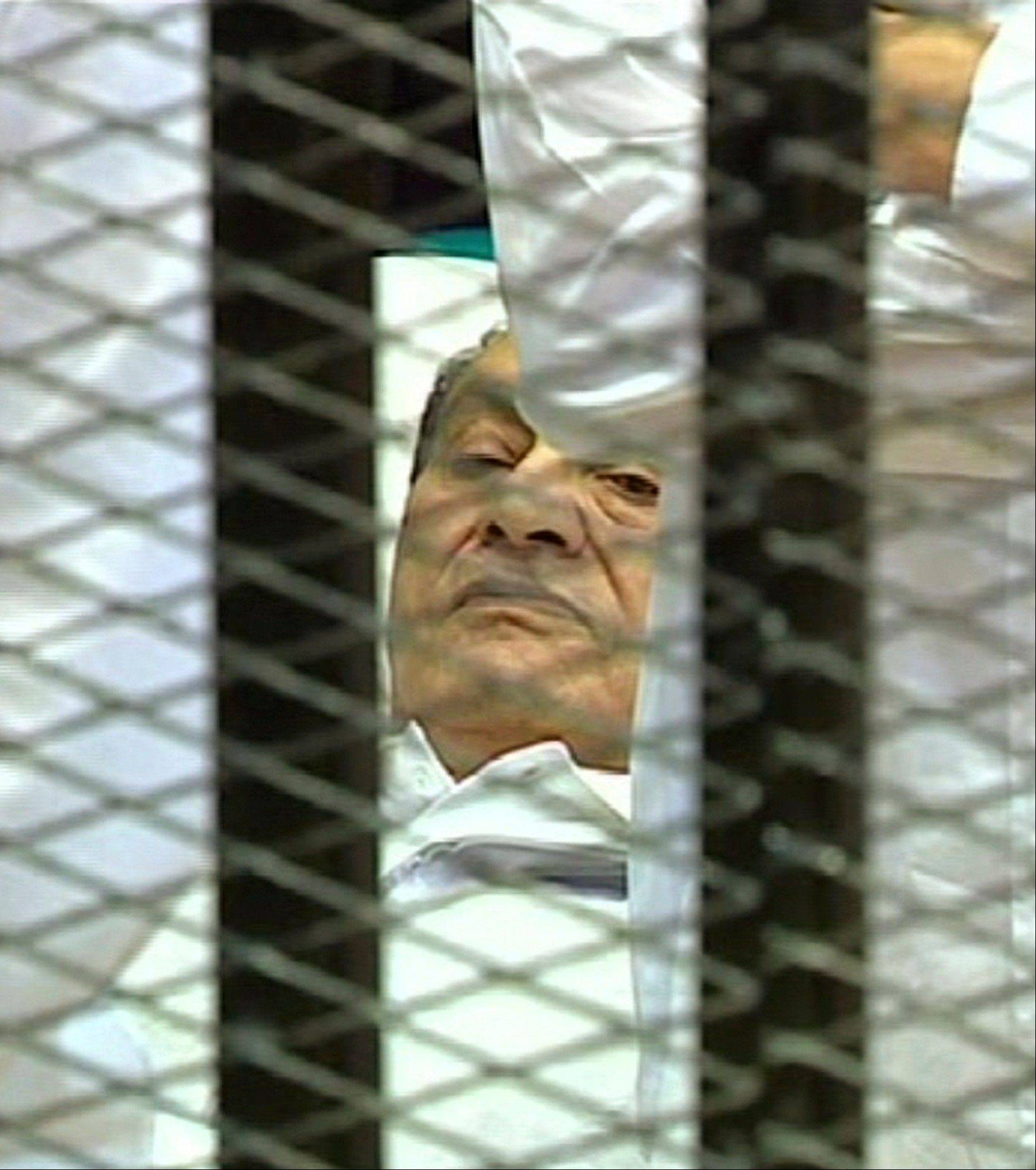 This video image taken from Egyptian State Television showing 83-year-old former Egyptian president Hosni Mubarak laying on a hospital bed inside a cage of mesh and iron bars in a Cairo courtroom Wednesday as his historic trial.
