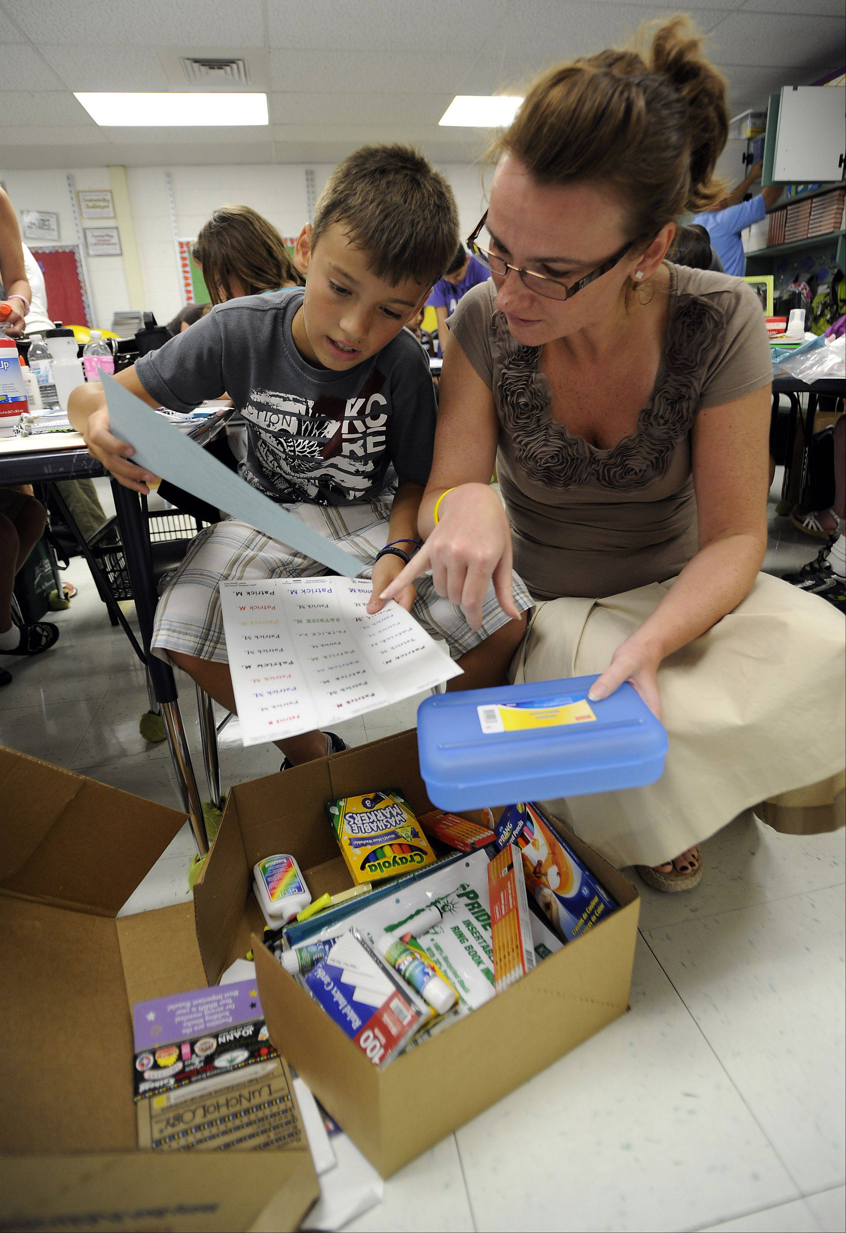 Ewa and her son Patrick Mack, 11, of Mount Prospect go over school supplies in his classroom at the Ridge Family Center for Learning in Elk Grove Village as part of the open house on Wednesday.