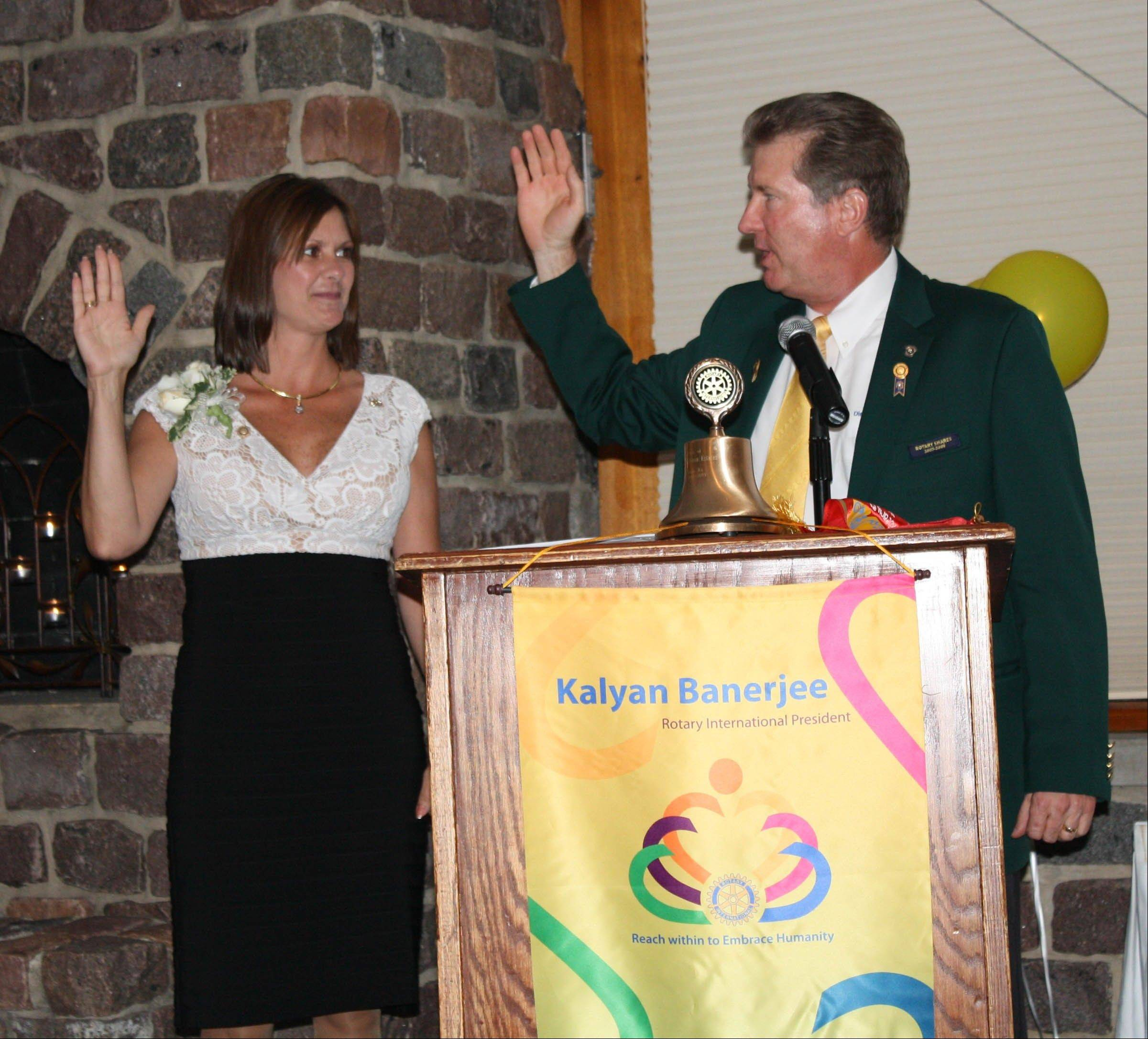 Past District Governor Michael Ericksen installs Julie Clark as president of the Schaumburg Hoffman Estates Rotary Club.