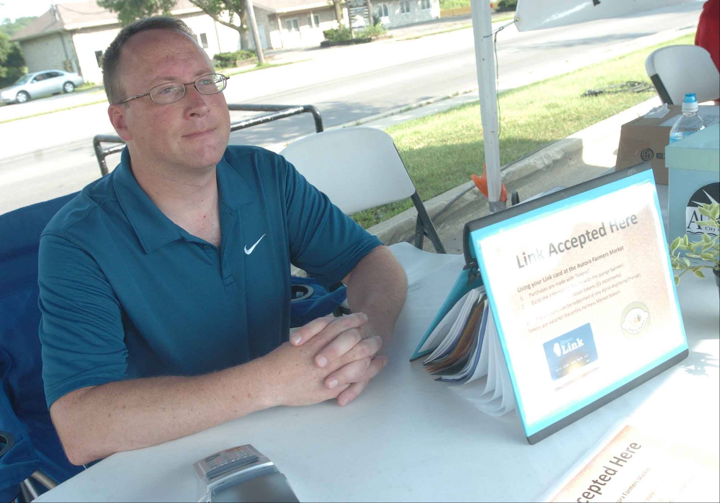 Volunteer Phil Supel of Aurora waits for people who want to use their Link cards to get tokens to allow them to buy food at the Aurora Farmers Market.
