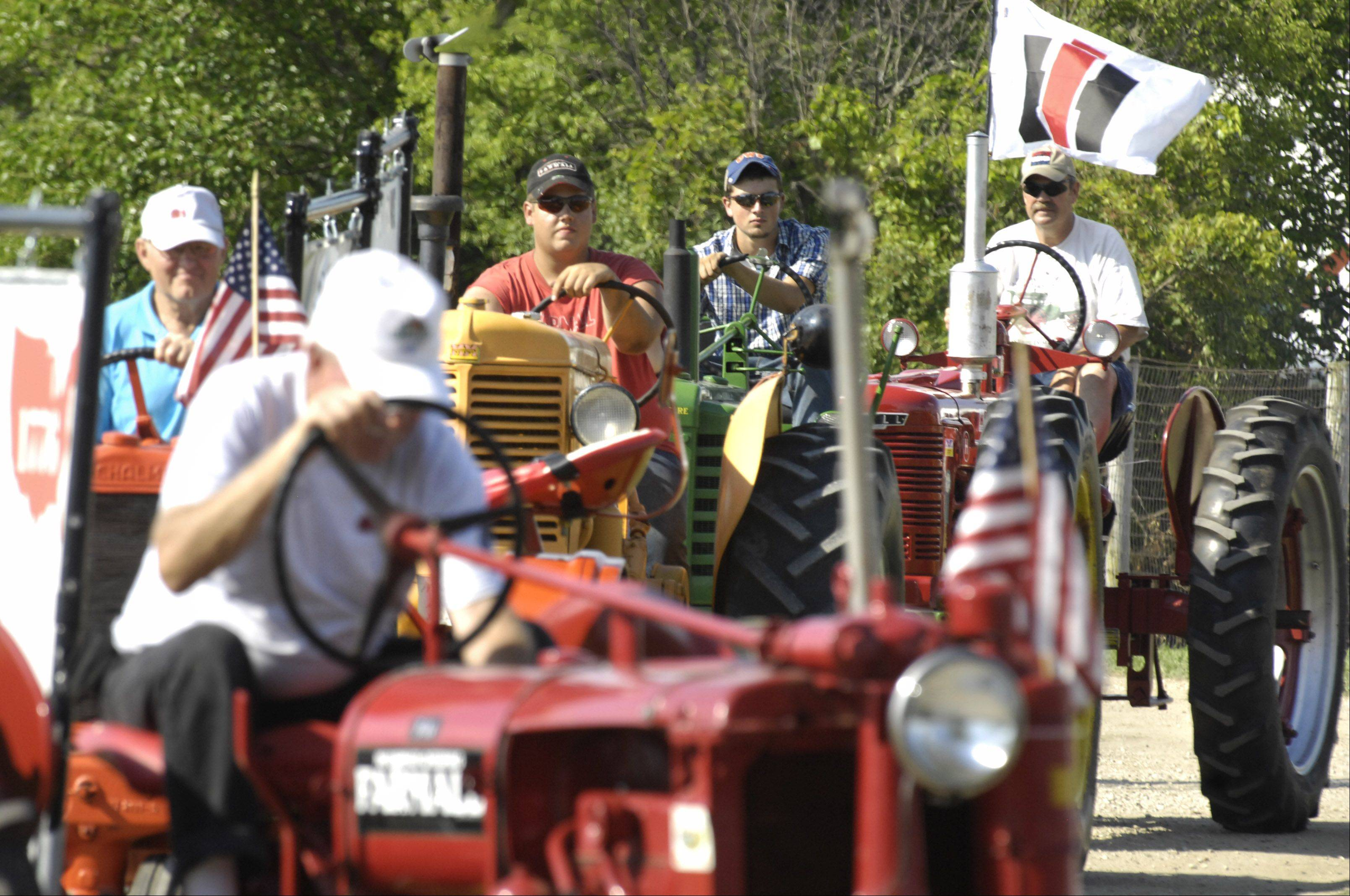 Fifteen antique tractors paraded around the McHenry County Fair in Woodstock Wednesday. They will parade the grounds each afternoon.