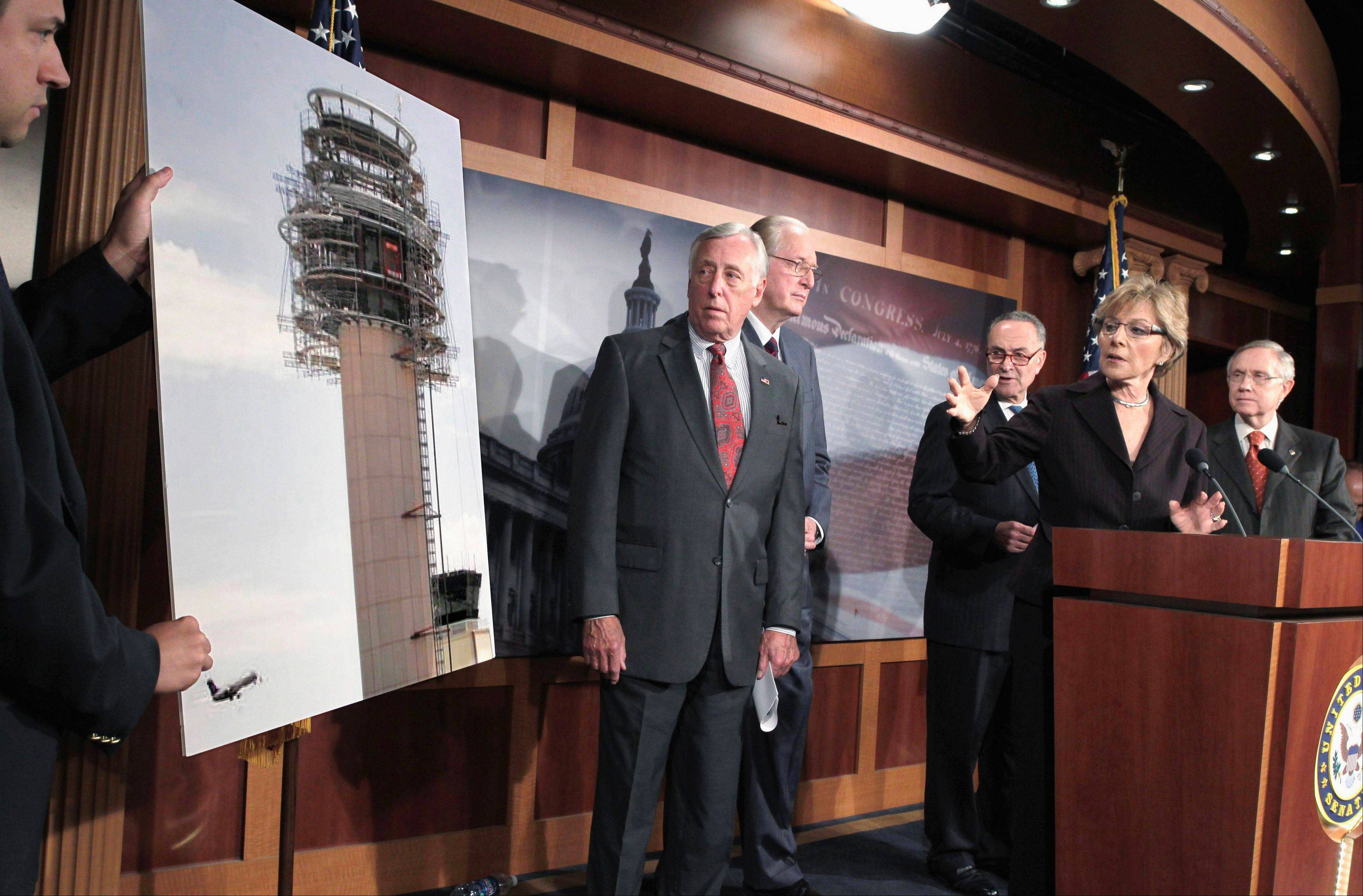 Democratic Sen. Barbara Boxer of California, second from right, points to a photo of a control tower being built in Palm Springs, Calif., that suffered some damage while under construction. ngton. The Senate approved legislation Friday ending a two-week partial shutdown of the Federal Aviation Administration, clearing the way for thousands of employees to return to work and hundreds of airport construction projects to resume.