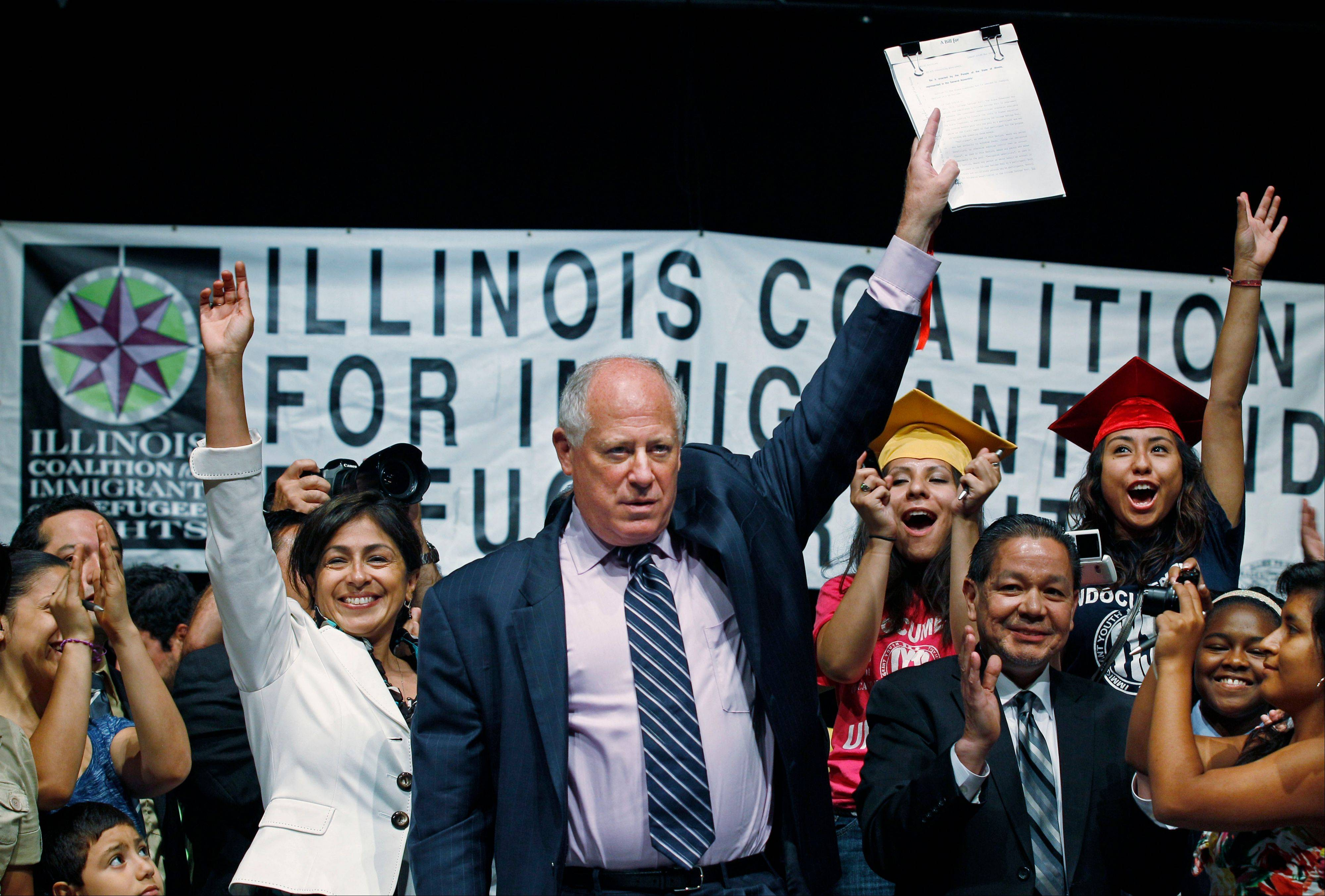 Gov. Pat Quinn celebrates with students and supporters after signing the Illinois Dream Act into law Monday at a Latino neighborhood high school in Chicago. The new law gives illegal immigrants access to private scholarships for college.