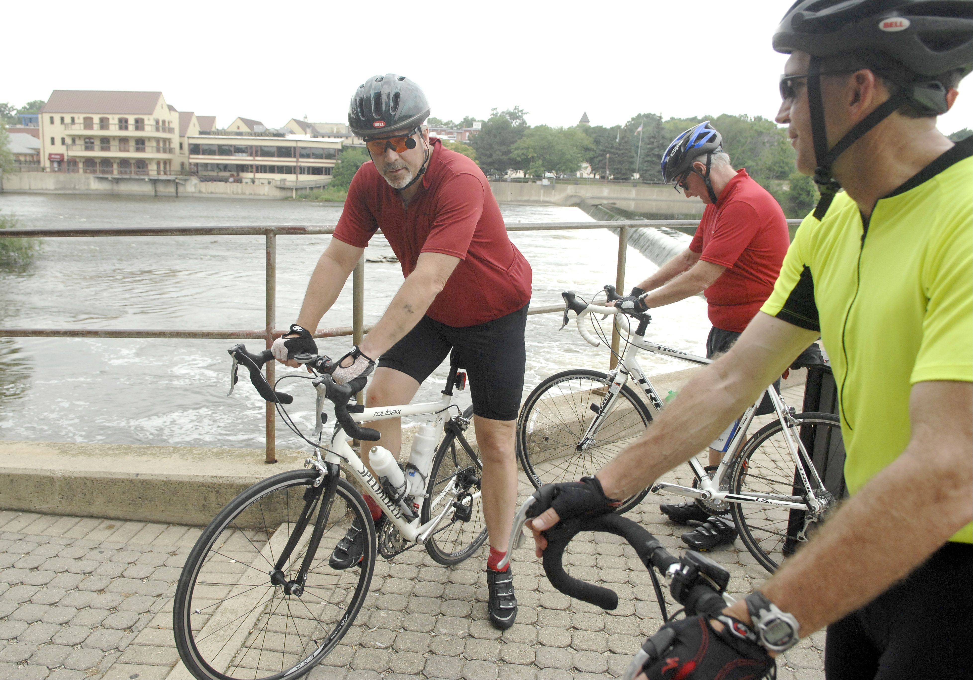 The Rev. Clint Roberts, left, and Brian Beaird, far right, both of Naperville, were two of the bicyclists involved in helping Friday in a Fox River rescue at the Geneva dam.