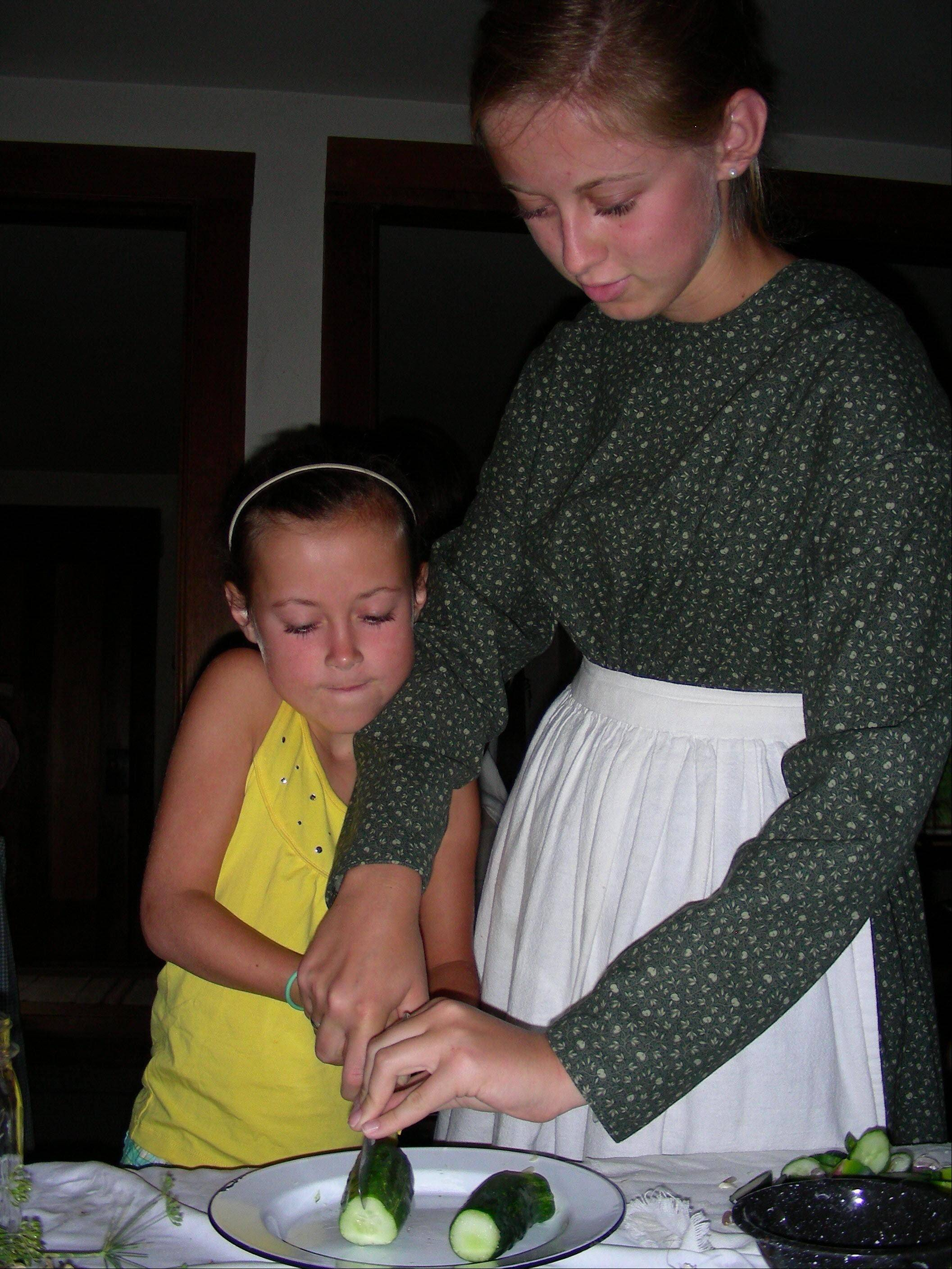 Volunteers Kate and Bethany Bussey demonstrate for the Durant House Museum �Pickling Party.� This year, the old-fashioned fun will be offered Sundays, Aug. 7 and 28.