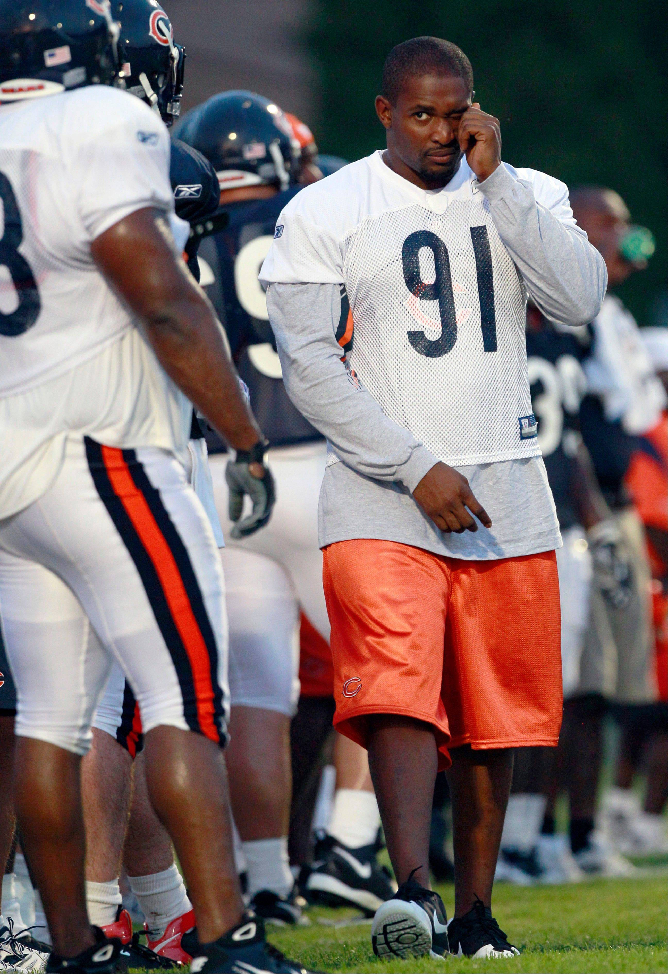 Chicago Bears' Amobi Okoye wipes his eye as he walks on the sideline during NFL football training camp Monday at Olivet Nazarene University in Bourbonnais.