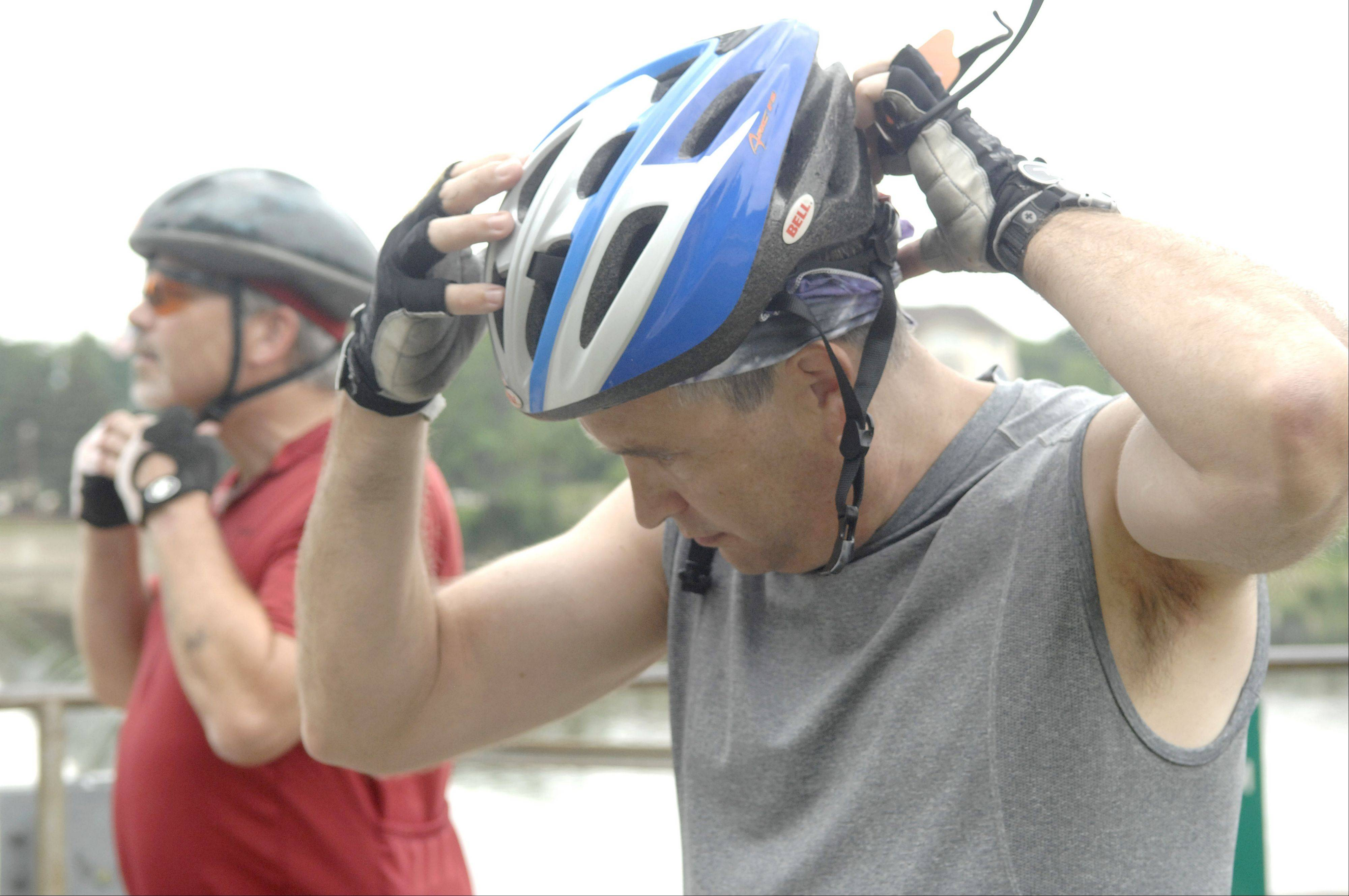 The Rev. Clint Roberts and Dan Pucci of Naperville don their bike helmets to return home hours after helping rescue a man and a boy from the Fox River in Geneva Friday.