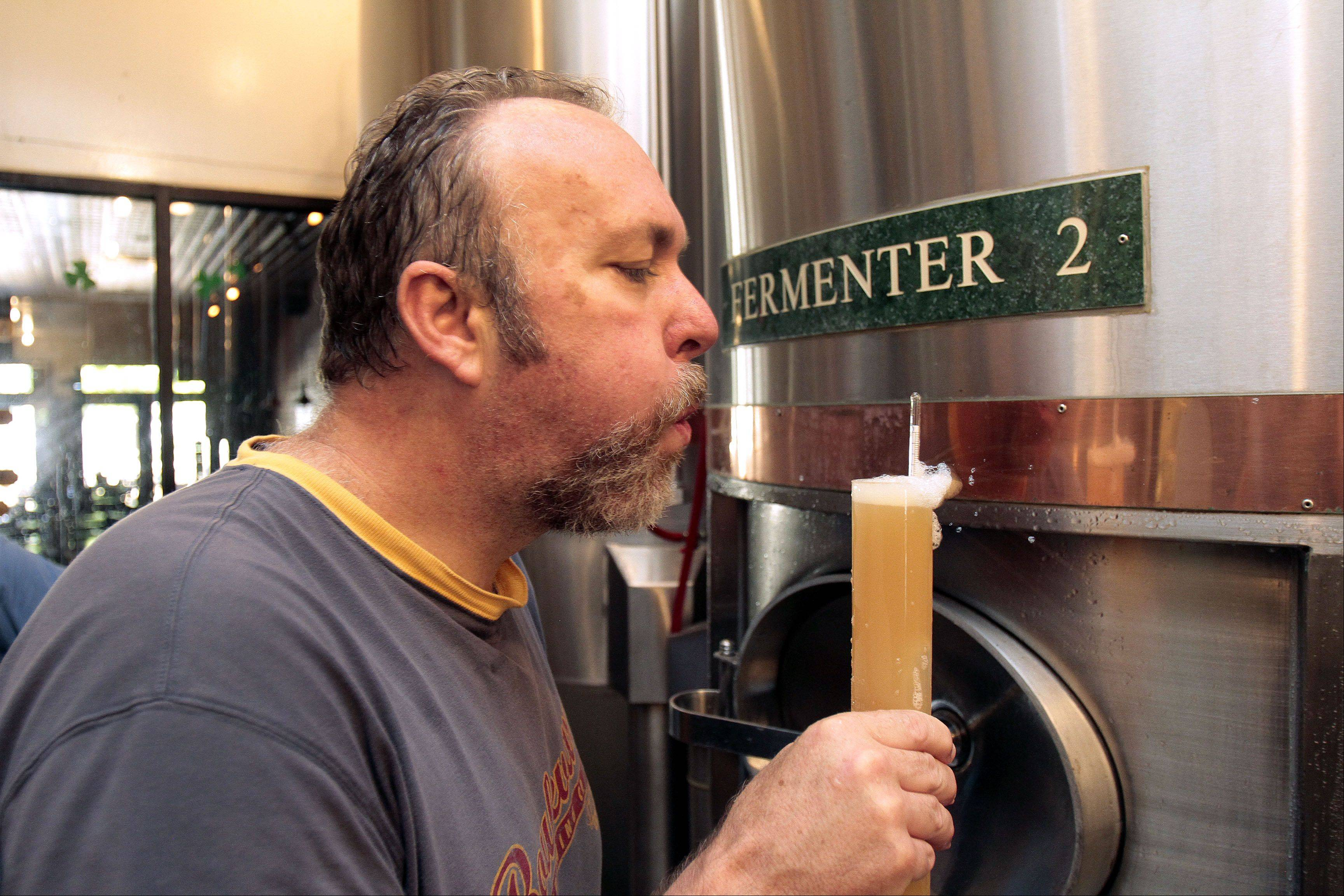 Brewmaster Greg Browne blows off foam from a test tube as he measures the alcohol content of his brew.