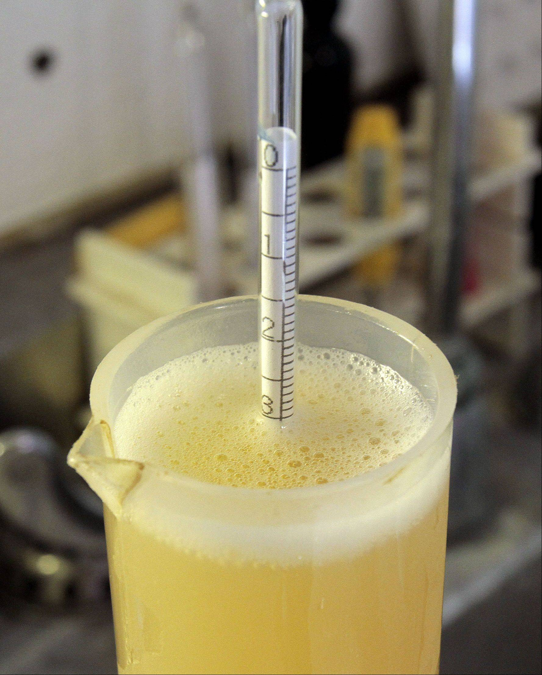 Alcohol content is checked with a bobber on a recent batch of beer.