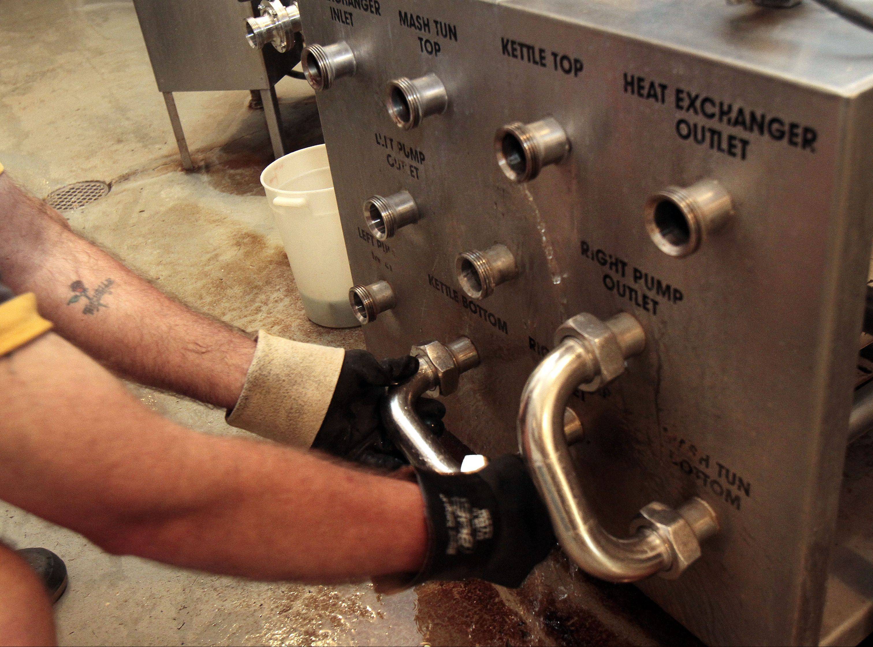 At left, Browne checks the mash tub with a flashlight where the brewing process begins. Above, a heat exchanger is used to cool down the wort before the yeast is added.