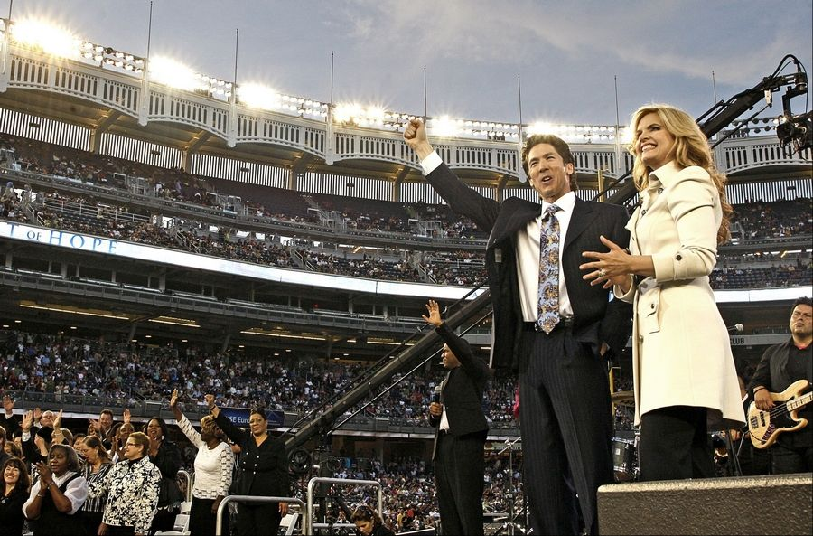 "Pastors Joel and Victoria Osteen speak to a crowd at Yankee Stadium during a recent ""Night of Hope"" event. The popular pastors will be at U.S. Cellular Field in Chicago Saturday night."