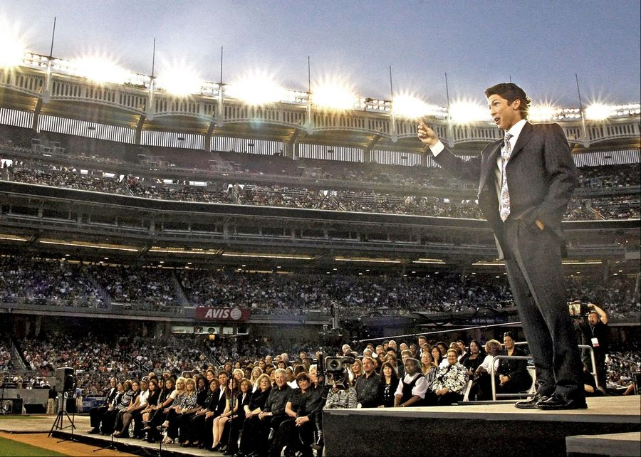 "TV Pastor Joel Osteen preaches to a crowd at Yankee Stadium during a recent ""Night of Hope"" event. The tour stops in Chicago Saturday night."