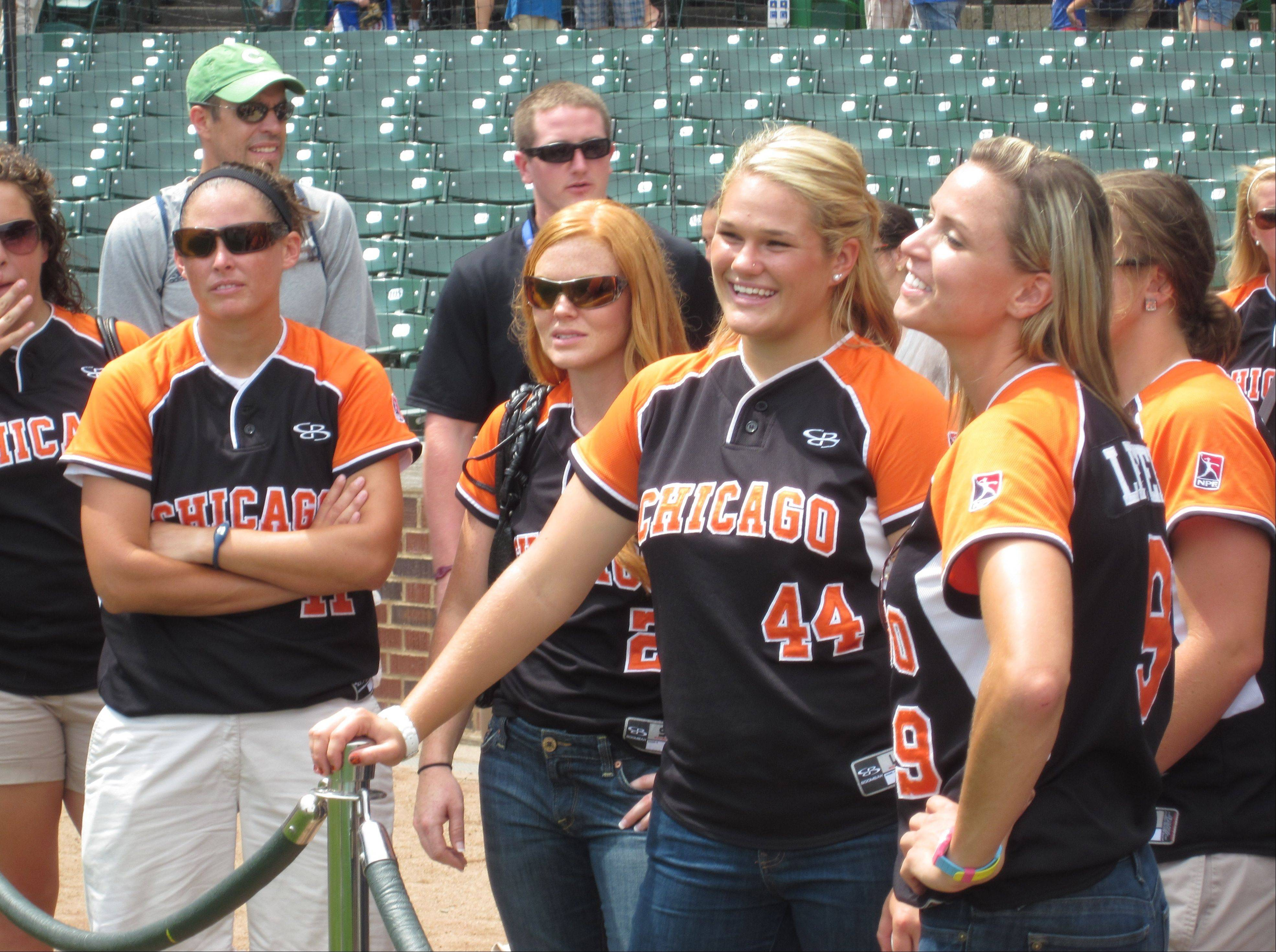 A day after recording a perfect game against Akron, Chicago Bandits players visited Wrigley Field on Friday to cheer for star pitcher Monica Abbott, who threw out the first pitch before the Cubs-Reds game. From left to right are: No. 11 Shannon Doepking, catcher; No. 2 Tammy Williams, infielder; No. 44 Nikki Nemitz, pitcher; and No. 9 Caitlin Lever, outfielder. The Bandit will play the Akron Racers in the second game of a four-game series tonight at Rosemont Stadium.