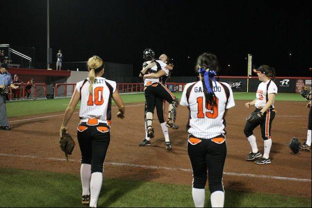 Bandits players rush the mound Thursday night at Rosemont Stadium after Monica Abbott gets the final out and records the first perfect game in the stadium, a 5-0 win over Akron.