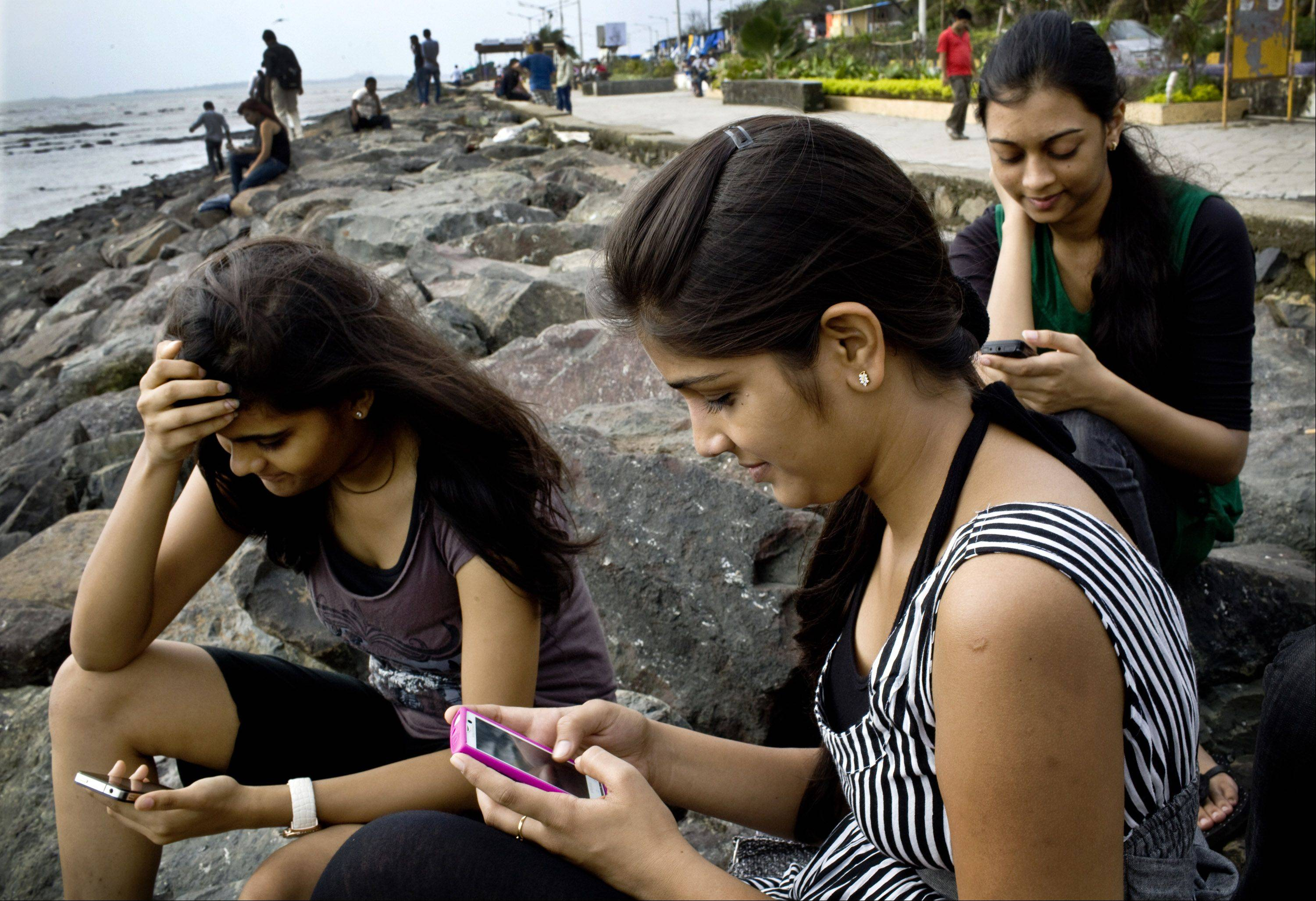 College students Saloni Shah, 18, from left, Roshani Munat, 18 and Shruti Jain, 19, check Facebook accounts on their smartphones in Mumbai, India, on Wednesday. India has 32 million Facebook users, according to socialbakers.com.