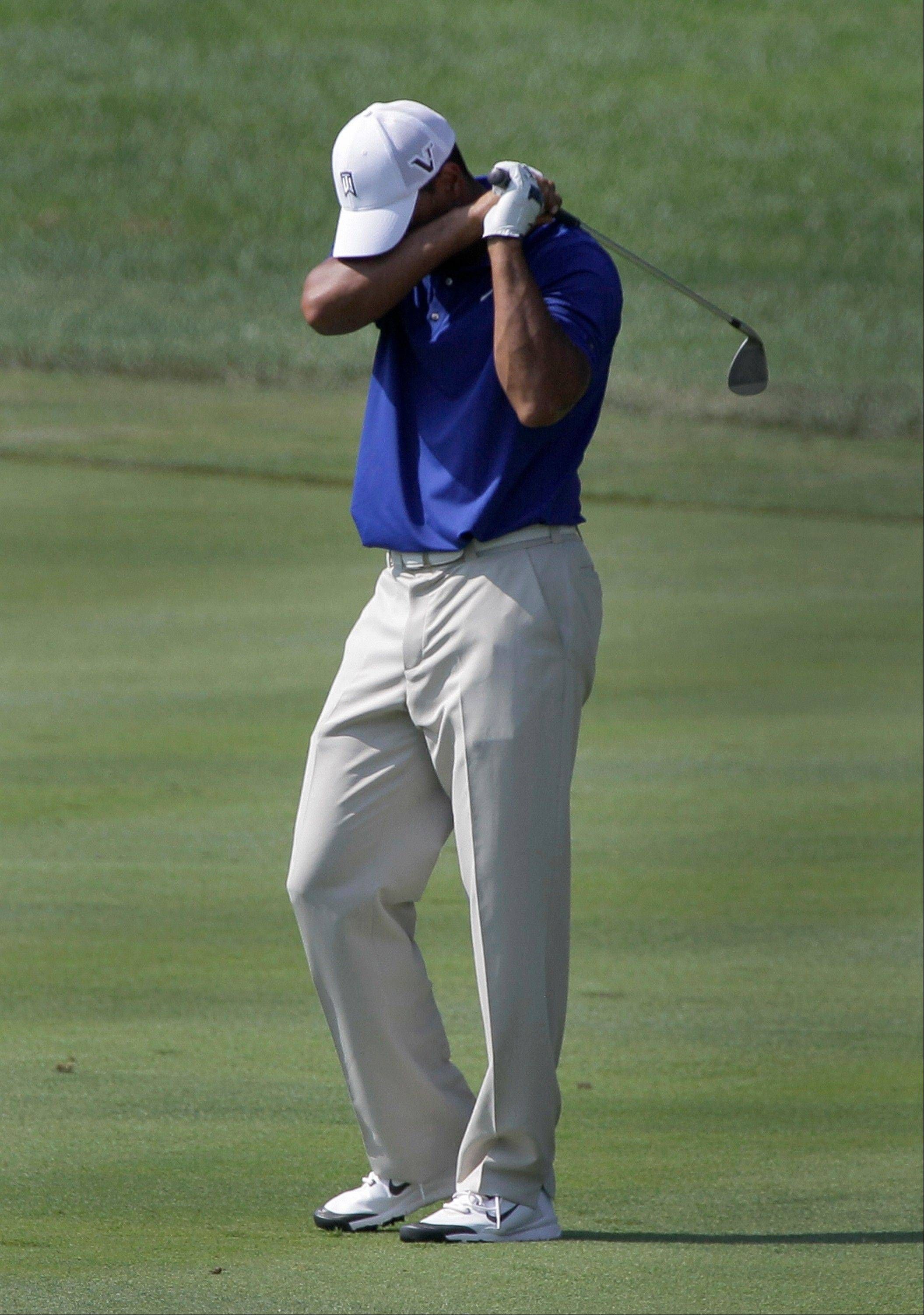 Tiger Woods reacts on the 16th fairway as his shot goes into a bunker Saturday in the Bridgestone Invitational golf tournament at Firestone Country Club in Akron, Ohio.