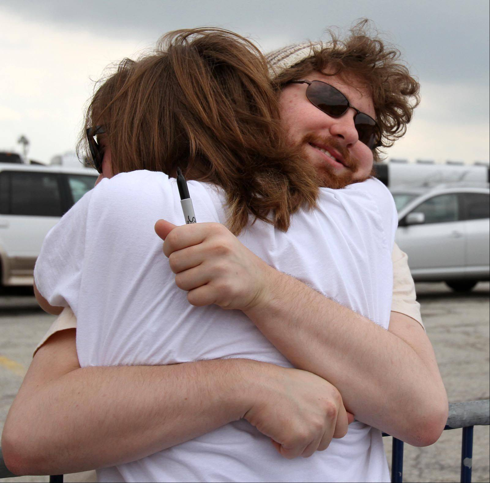Angela Rublaitus, 13, of Hoffman Estates, gets a hug from Casey Abrams before the American Idol concert.