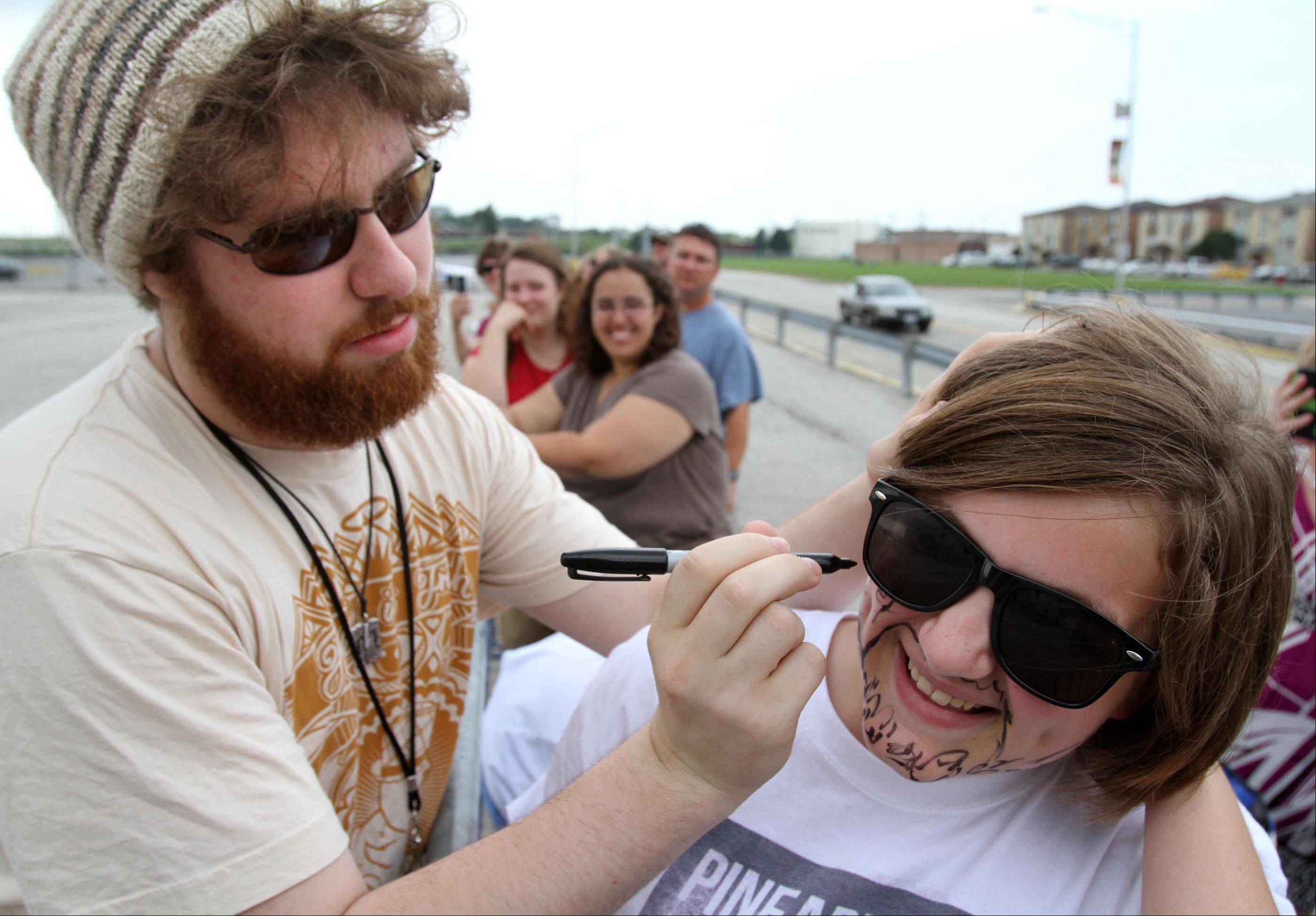 Angela Rublaitus, 13, of Hoffman Estates, has Casey Abrams autograph and draw on her face.